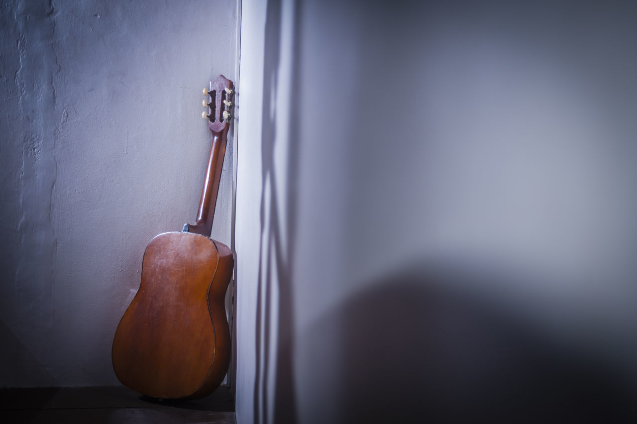 Acoustic Guitar Against Wall At Home