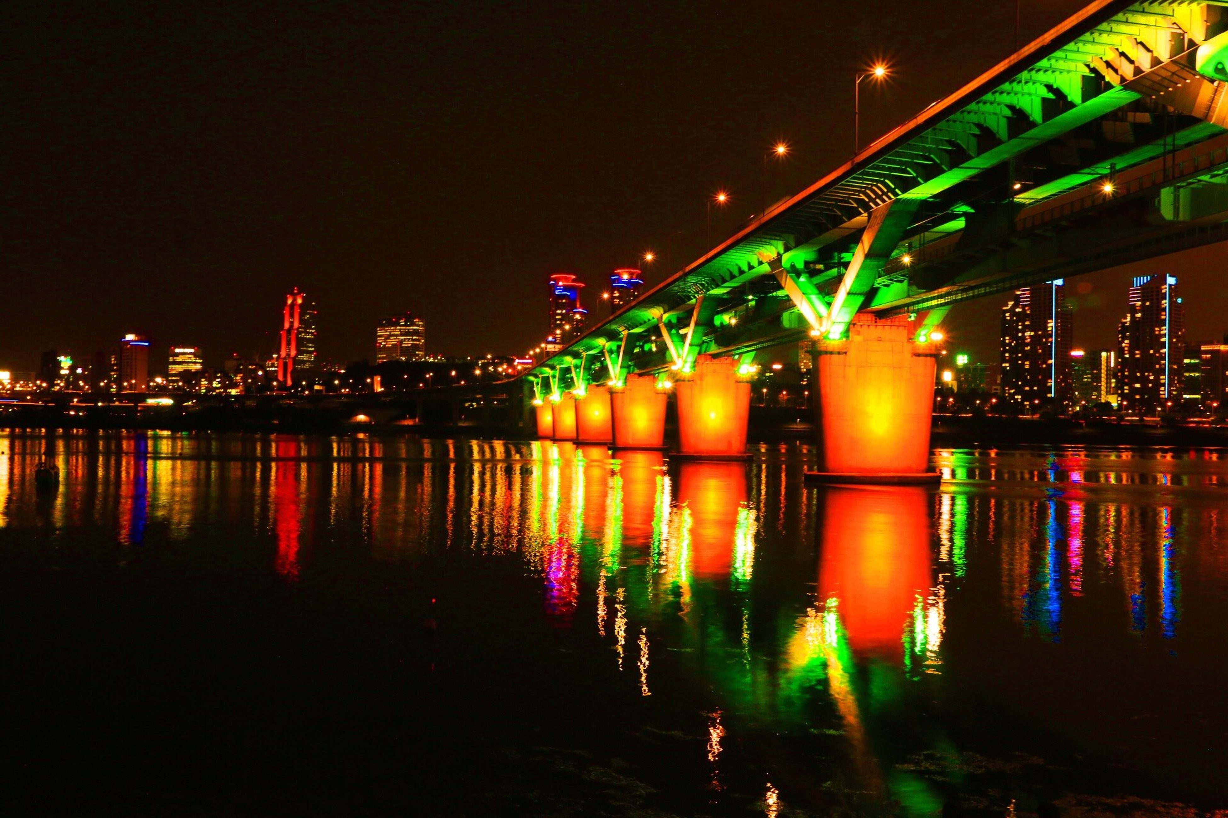 illuminated, night, reflection, water, architecture, built structure, building exterior, waterfront, river, city, lighting equipment, connection, bridge - man made structure, sky, multi colored, light, street light, outdoors, light - natural phenomenon, clear sky
