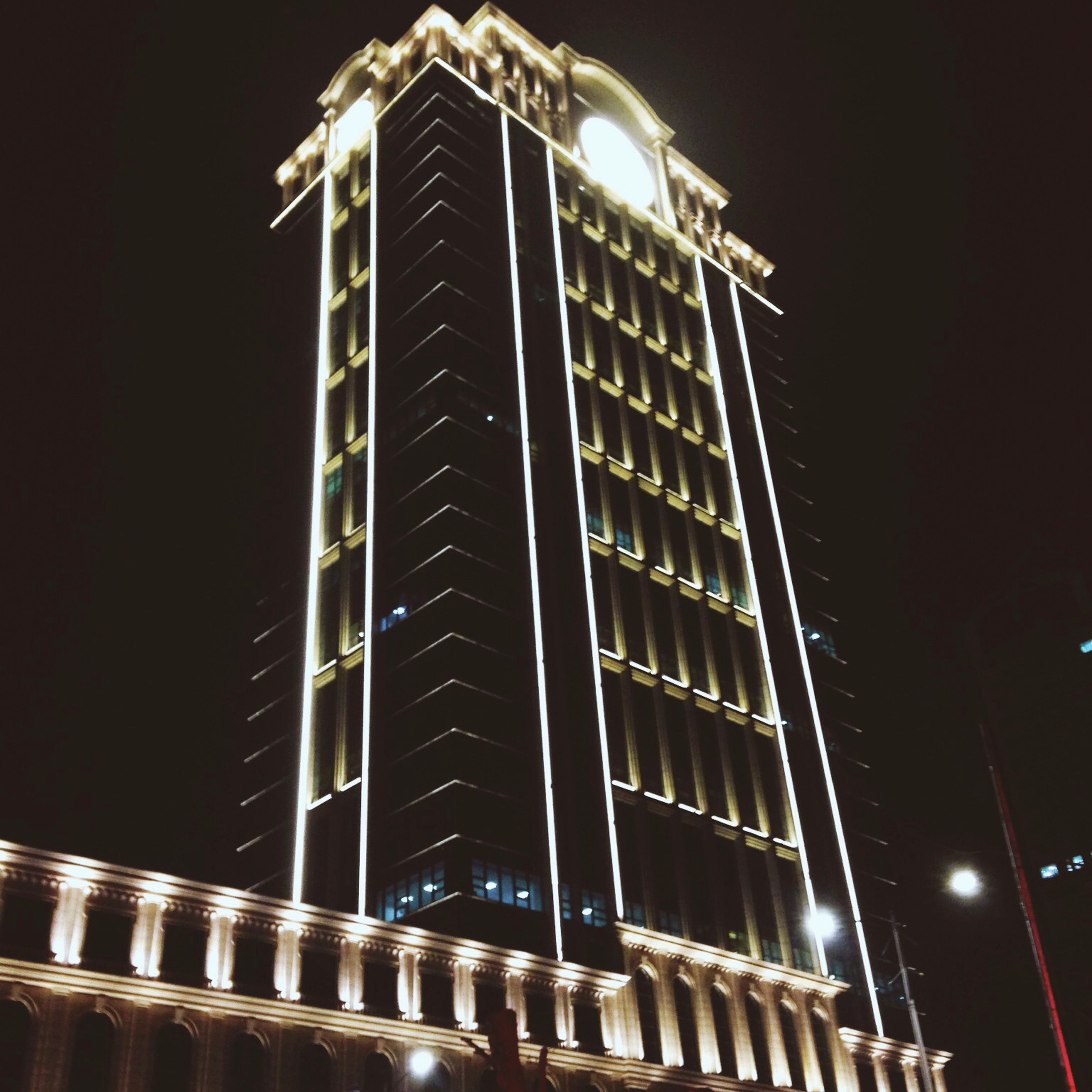 night, illuminated, low angle view, architecture, built structure, building exterior, building, city, clear sky, lighting equipment, dark, sky, tall - high, tower, street light, modern, skyscraper, no people, outdoors, light - natural phenomenon