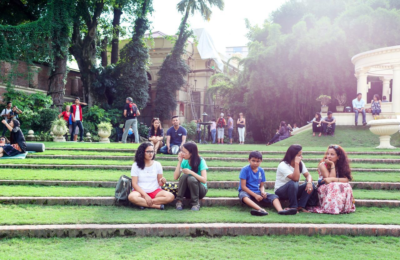 tree, large group of people, sitting, real people, casual clothing, day, grass, full length, men, outdoors, park - man made space, lifestyles, girls, togetherness, building exterior, built structure, relaxation, women, childhood, nature, student, sky, people, adult