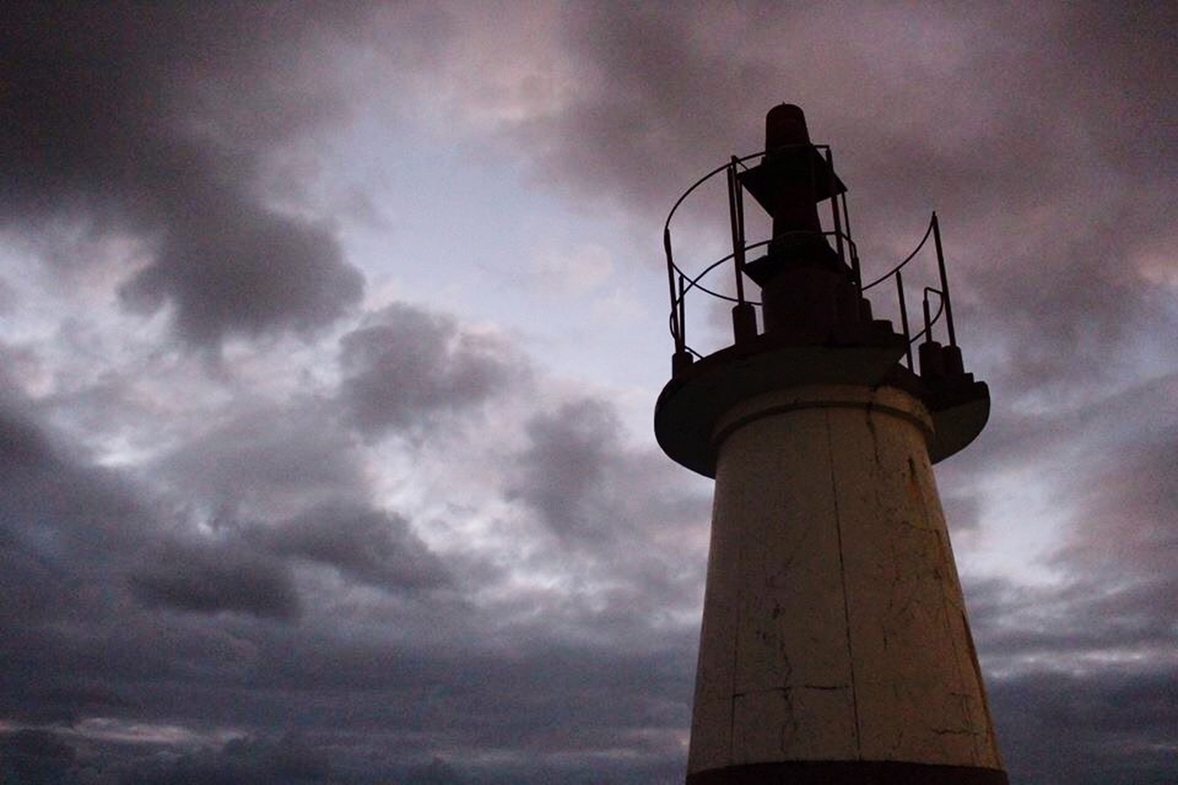 sky, low angle view, cloud - sky, architecture, built structure, tower, cloudy, lighthouse, communications tower, tall - high, building exterior, guidance, communication, cloud, sunset, industry, weather, dusk, direction, overcast