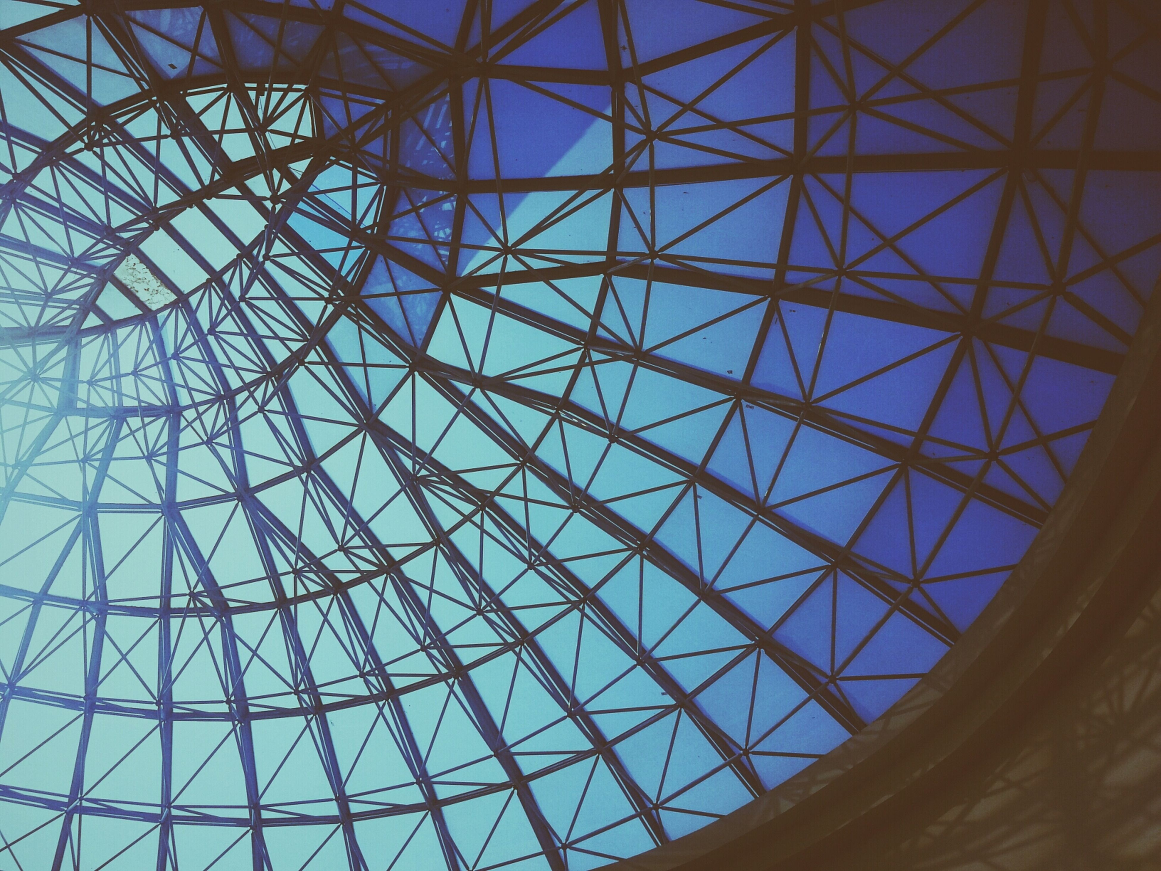 low angle view, architecture, built structure, indoors, pattern, glass - material, ceiling, full frame, backgrounds, architectural feature, design, geometric shape, modern, directly below, transparent, skylight, grid, sky, no people, day