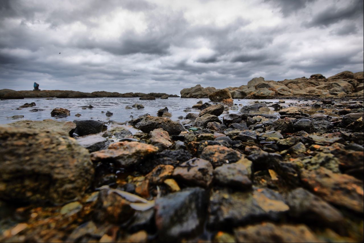 pebble, nature, surface level, beach, cloud - sky, rock - object, sky, outdoors, day, water, no people, sea, pebble beach, textured, tranquility, beauty in nature, close-up