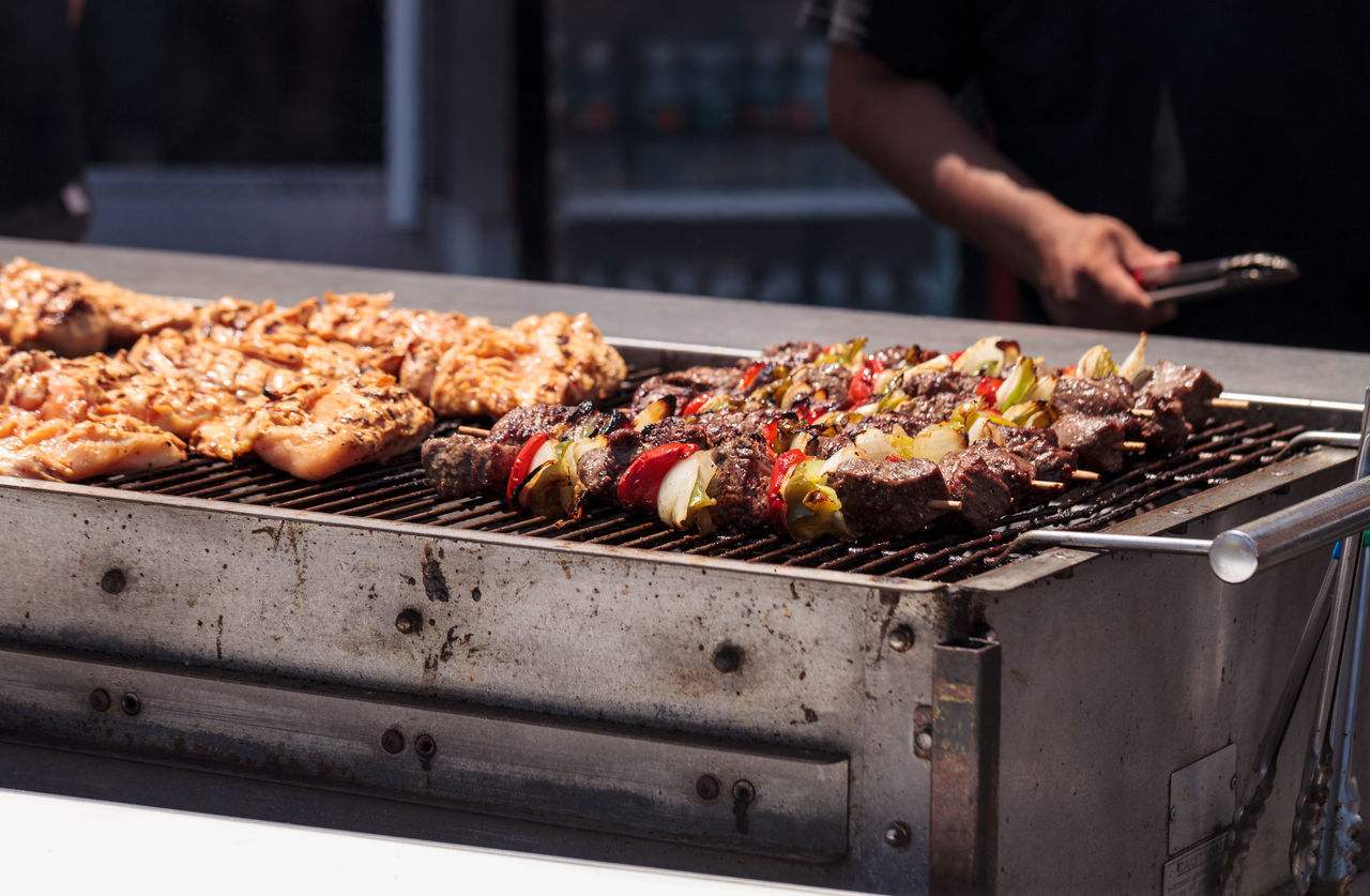 Chicken, beef and onion kabobs on a barbecue grill cooking at a fair ground. Adult Barbecue Barbecue Grill Barbeque BBQ Beef Chicken Cooking Day Food Freshness Grill Grill Meat Grilled Healthy Eating Kabob Meal Outdoors People Preparing Food Skewer