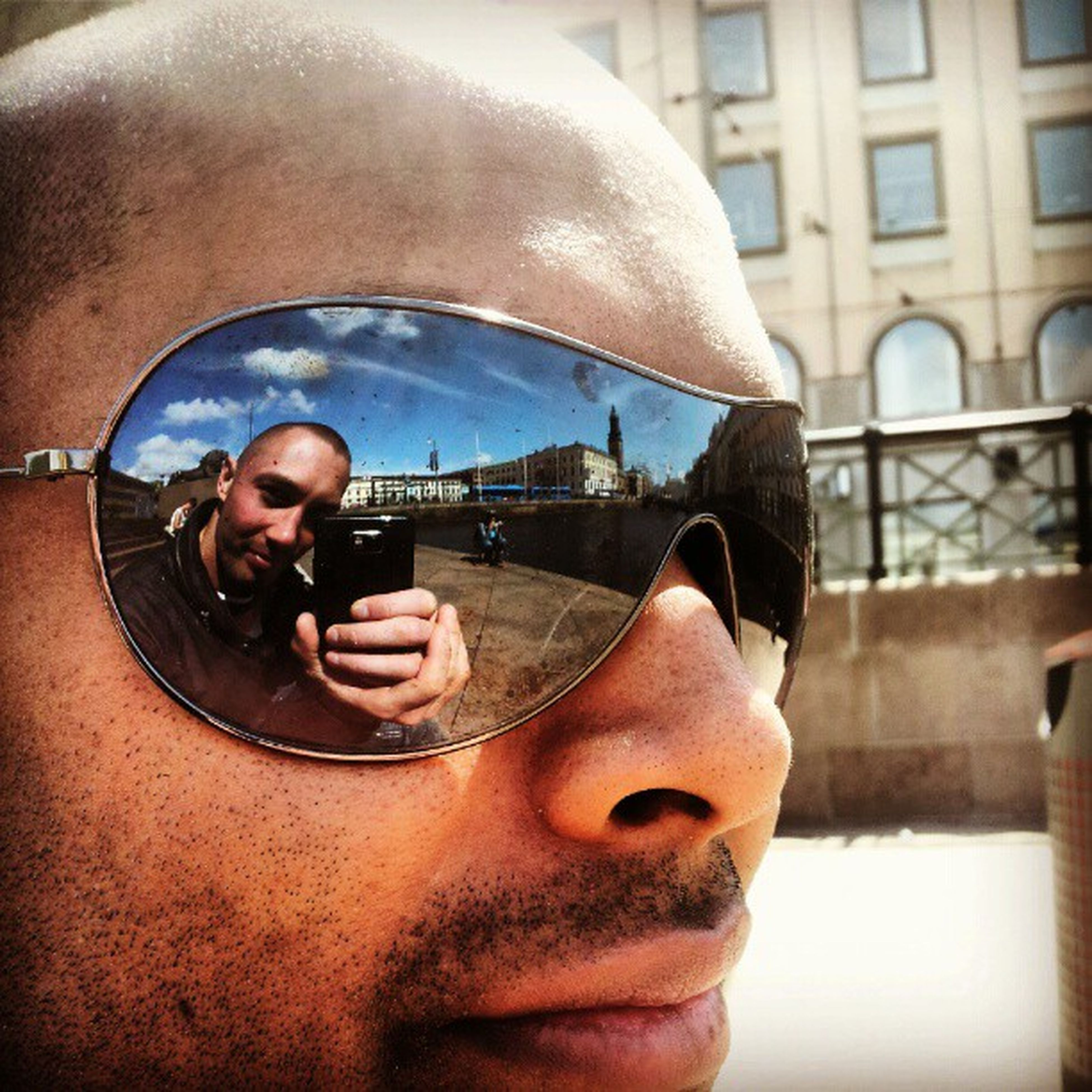lifestyles, person, young adult, sunglasses, leisure activity, young men, looking at camera, portrait, front view, headshot, photography themes, holding, photographing, reflection, smiling, smart phone, mid adult men, architecture