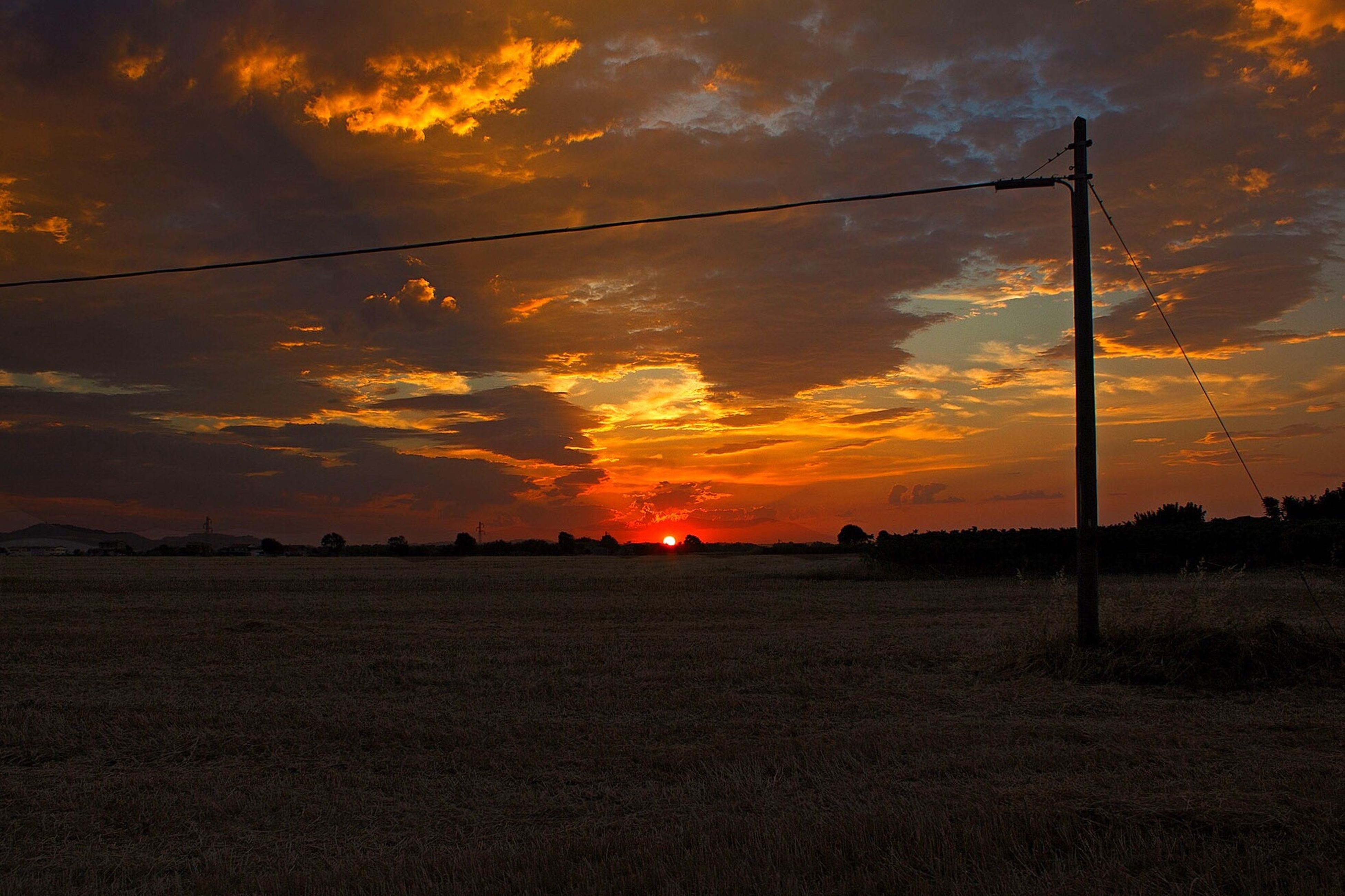 sunset, field, sky, nature, cloud - sky, orange color, beauty in nature, scenics, tranquility, landscape, no people, tranquil scene, silhouette, cable, outdoors, agriculture, rural scene, tree, grass, day
