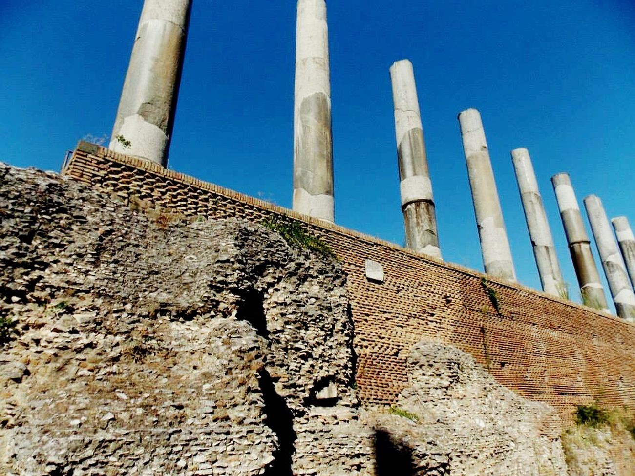 Architecture Roman Ruins Historic City Historical Ruins Columns Blue Sky Daylight Built Structure Clear Sky Day Outdoors No People History Ancient Civilization Travel Tourism Travel Destinations Architectural Column Old Architecture Travel Photography Europe Rome Italy