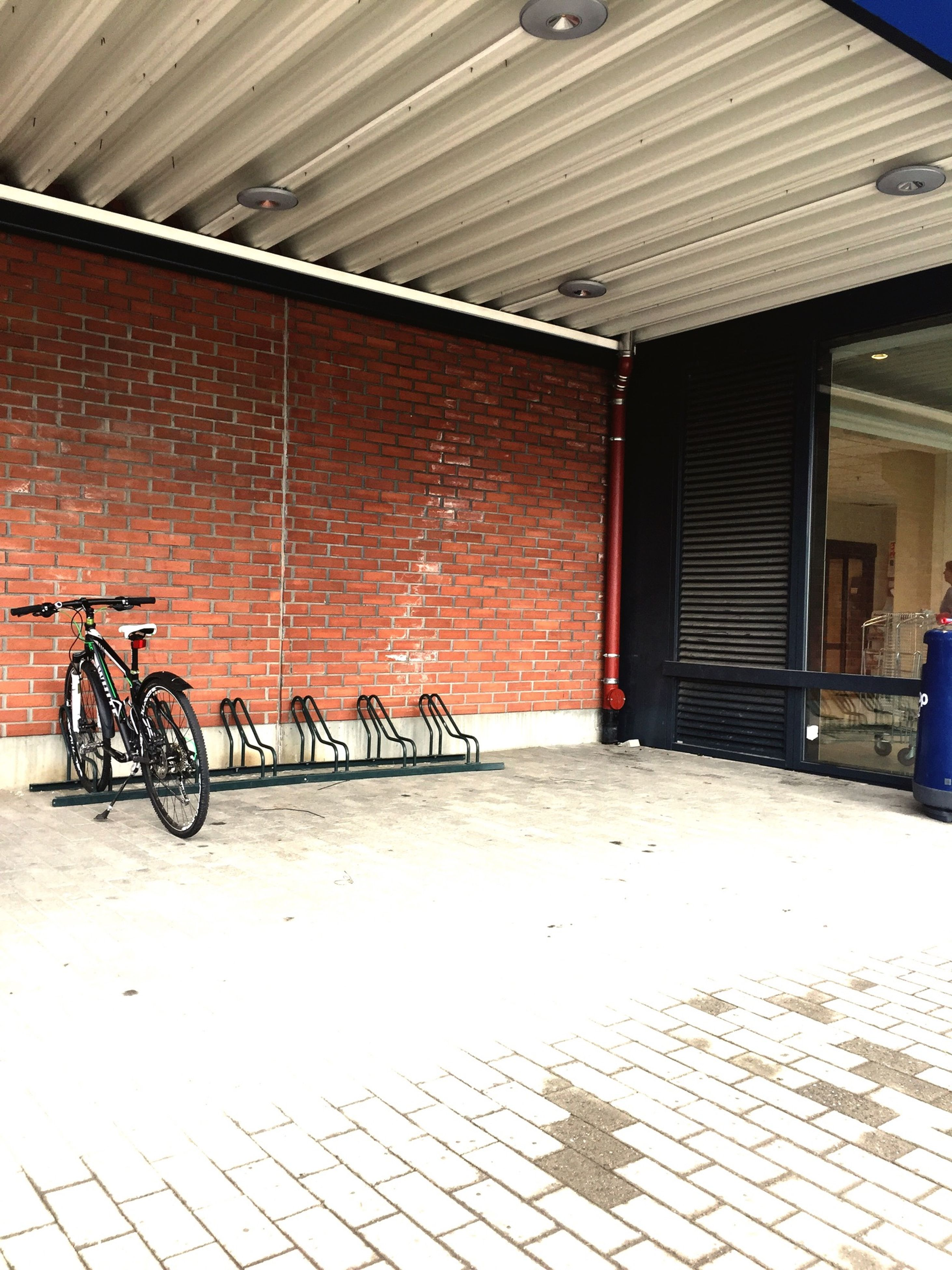 architecture, built structure, transportation, bicycle, empty, absence, parking lot, building exterior, indoors, stationary, door, graffiti, wall - building feature, closed, parking, mode of transport, cobblestone, no people, illuminated, street