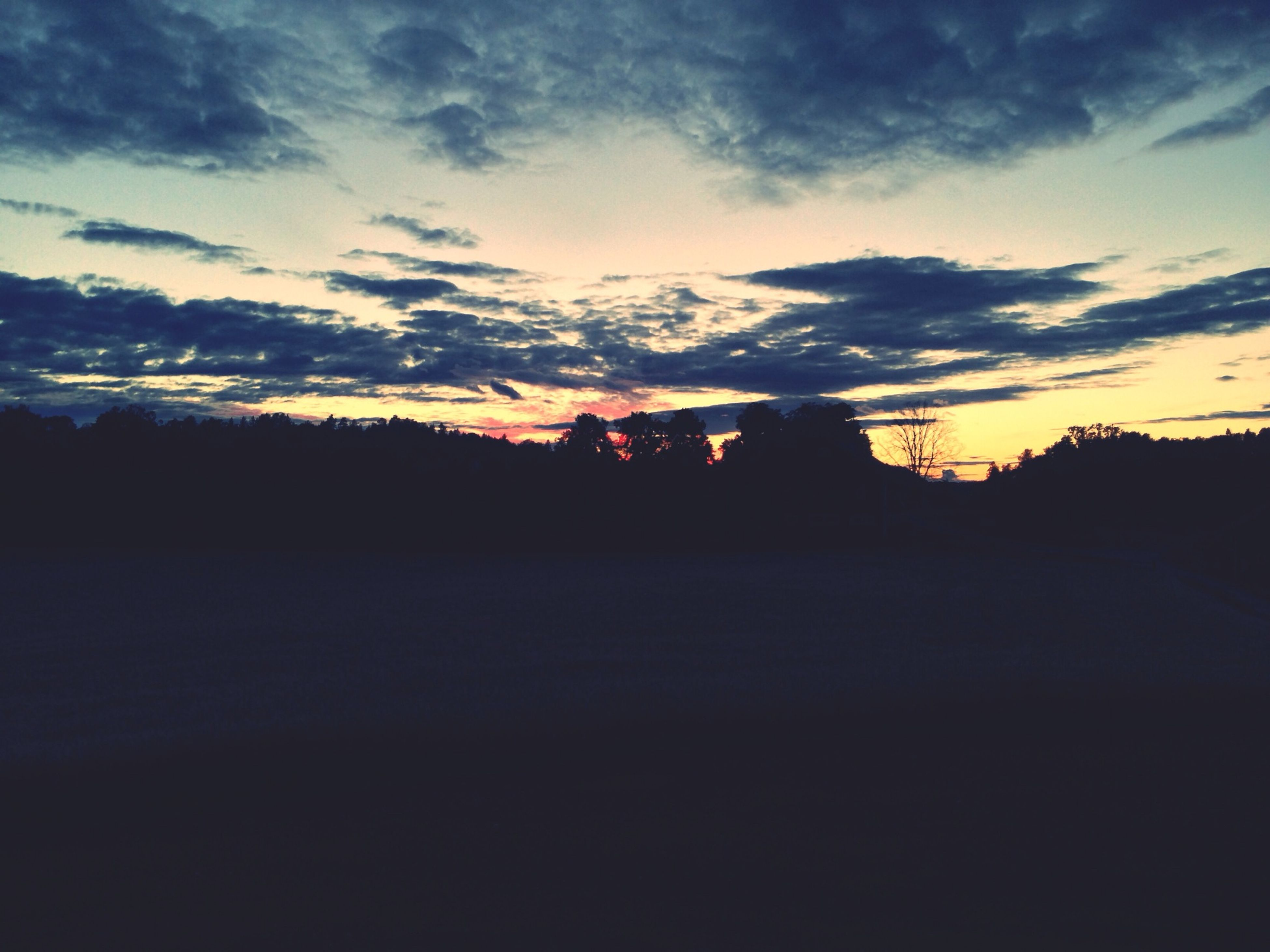 sunset, silhouette, sky, cloud - sky, orange color, tranquility, tranquil scene, scenics, cloud, beauty in nature, landscape, dark, nature, tree, dusk, dramatic sky, built structure, outdoors, idyllic, cloudy