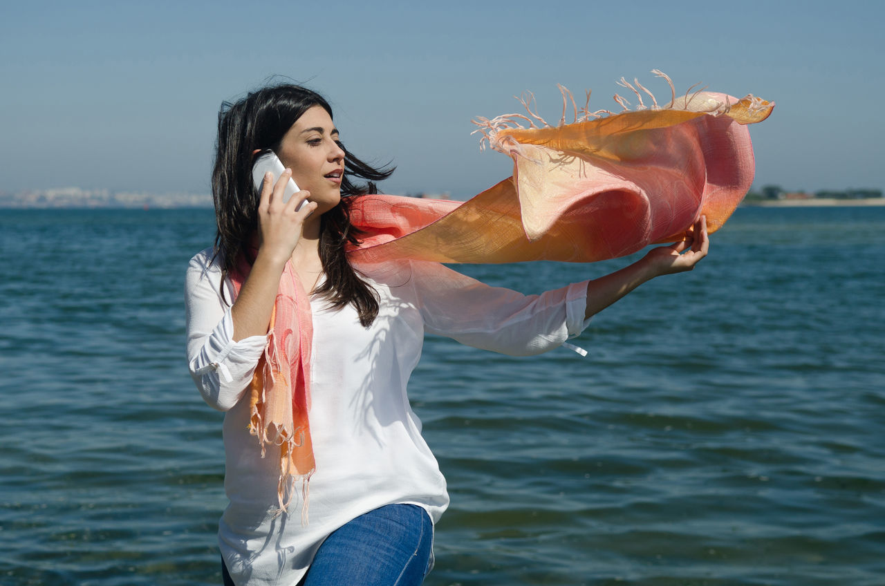 Casual beautiful woman talking on the phone Adult Adults Only Beautiful Woman Casual Clothing Day Fashion Holding Horizon Over Water Leisure Activity Lifestyles Long Hair Nature One Person Outdoors People Phone Real People Sea Sky Standing Talking Water Waterfront Young Adult Young Women