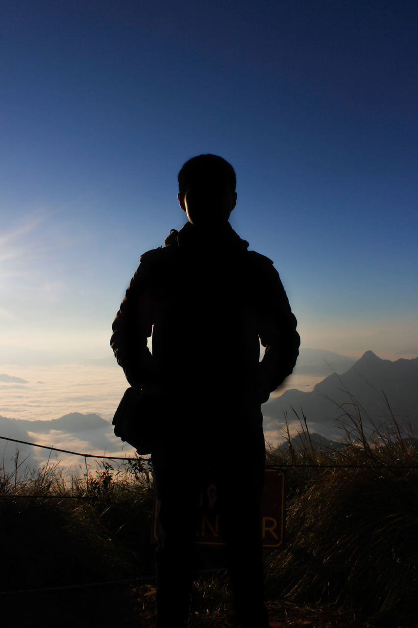 Silhouette Man Standing On Mountain Against Blue Sky