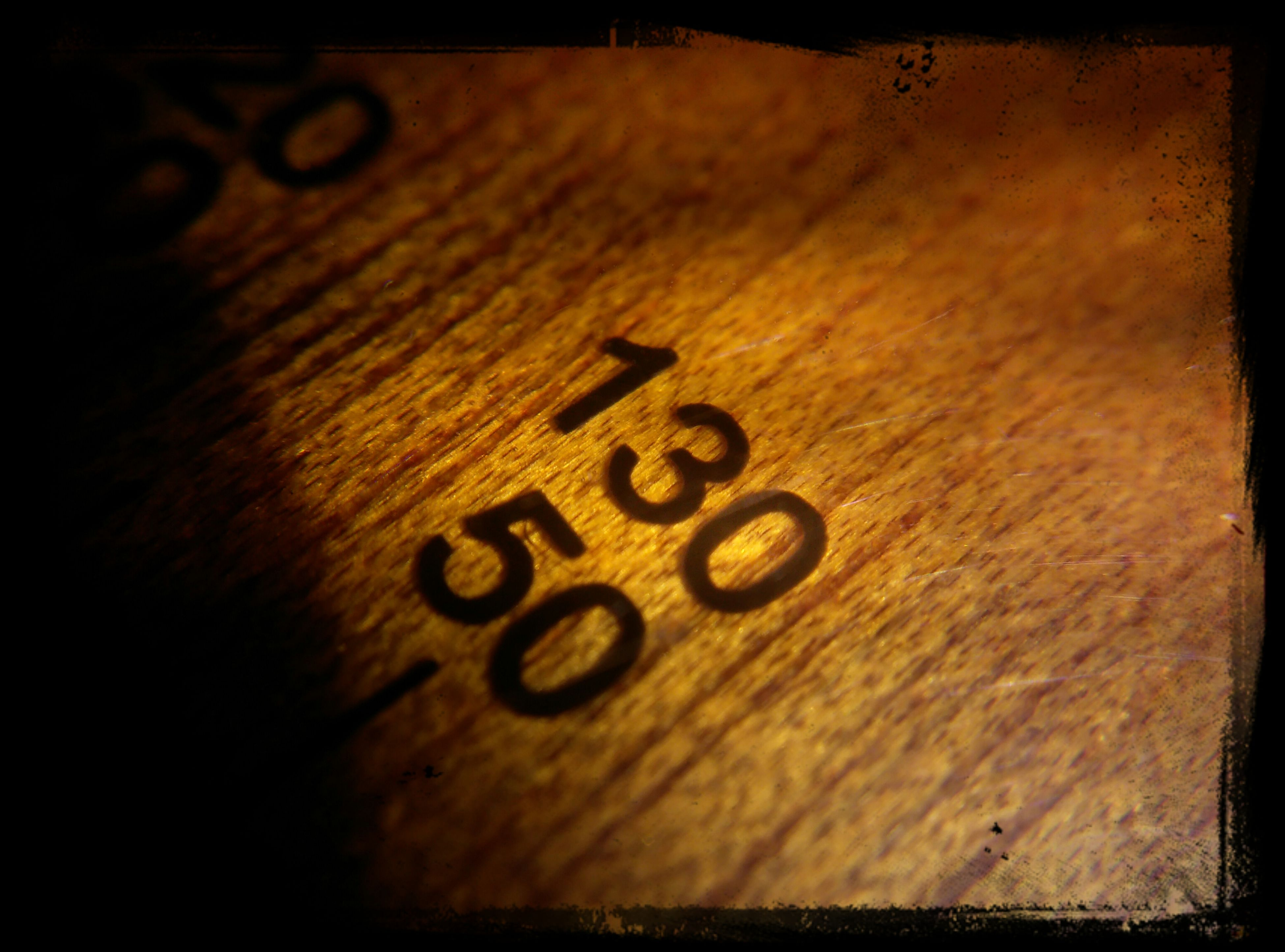 indoors, table, wood - material, still life, close-up, high angle view, wooden, text, selective focus, shadow, auto post production filter, no people, communication, wood, single object, western script, number, transfer print, textured, wall - building feature