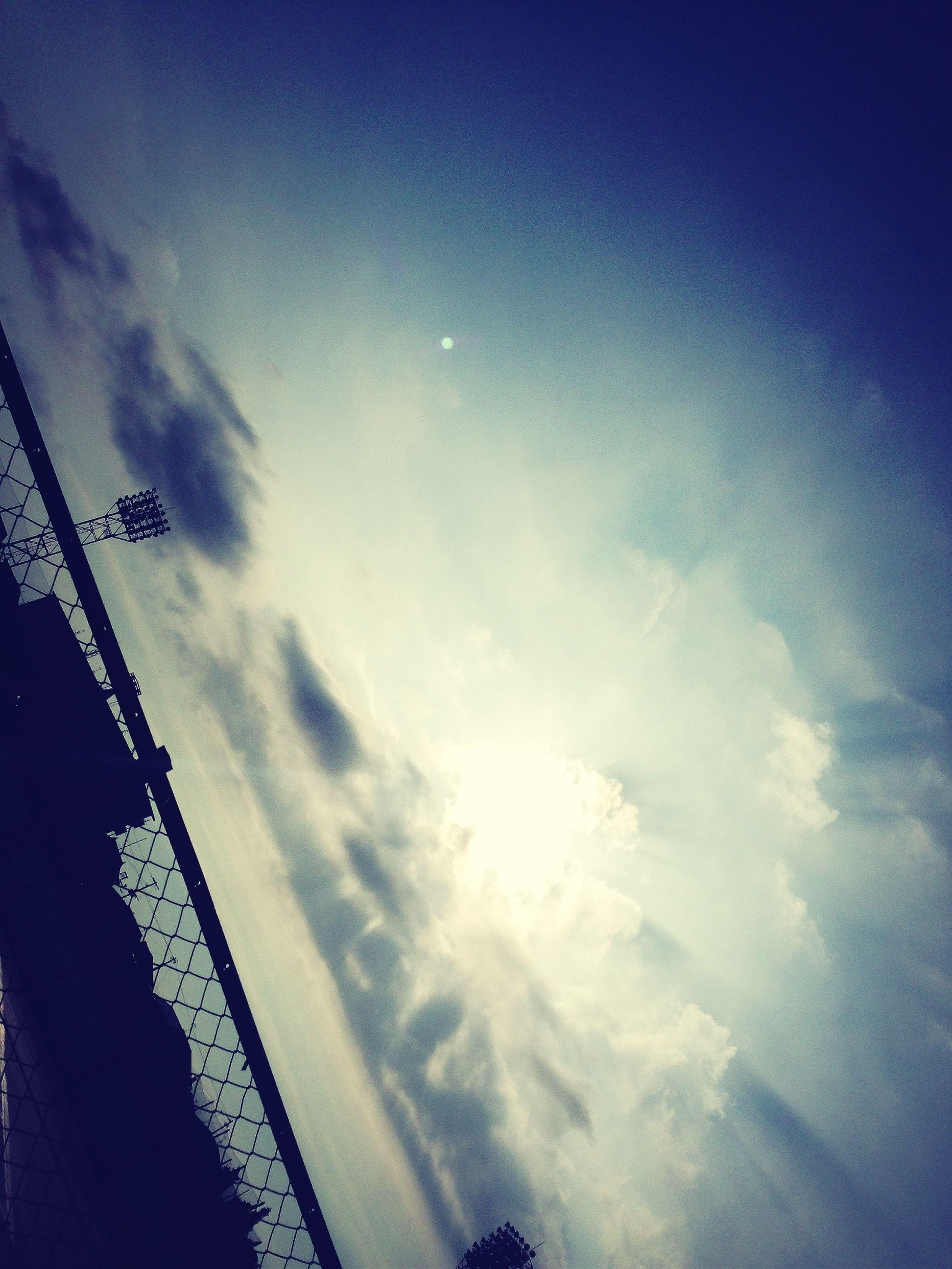 low angle view, sky, blue, cloud - sky, built structure, architecture, building exterior, cloud, sunlight, outdoors, transportation, city, silhouette, day, no people, vapor trail, nature, sunbeam, sun, cloudy