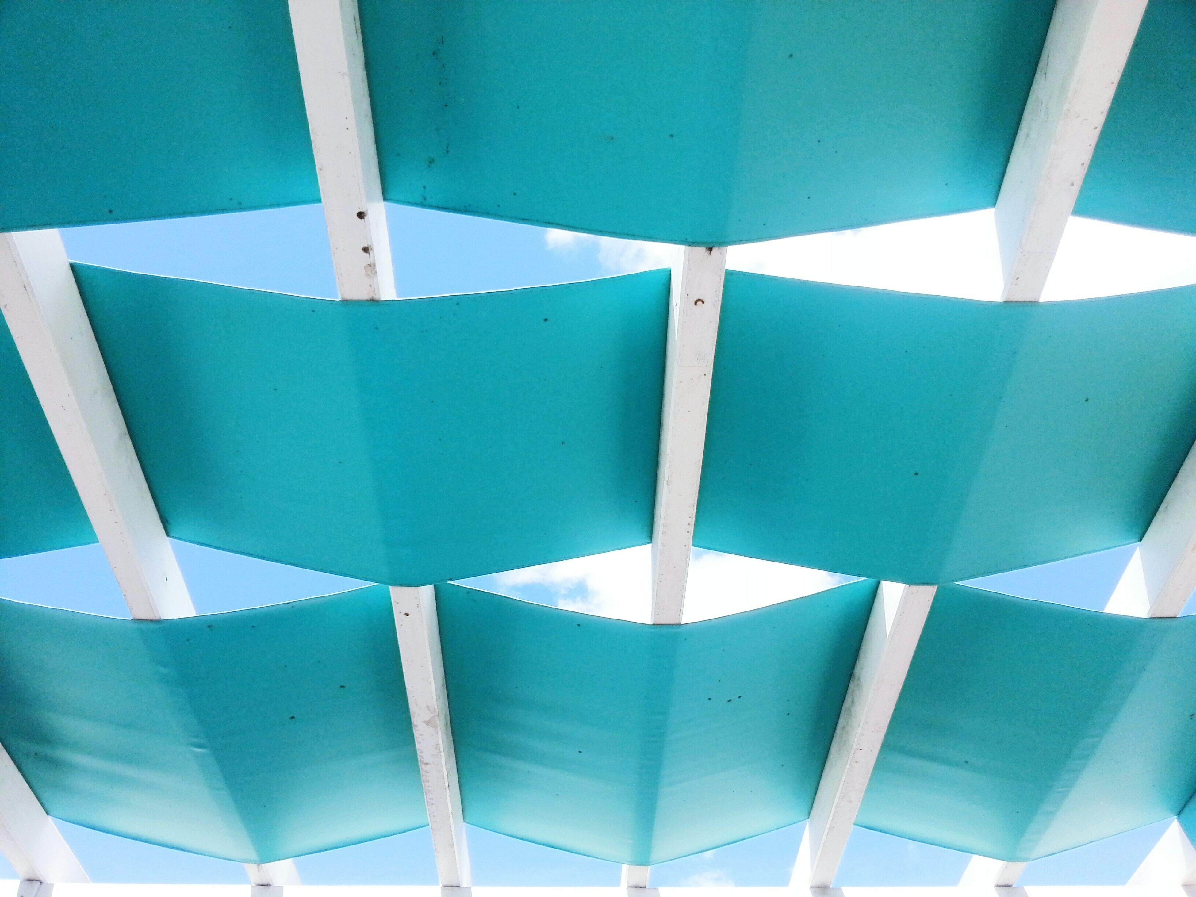 blue, indoors, low angle view, built structure, pattern, ceiling, architecture, design, day, no people, repetition, chair, in a row, empty, full frame, absence, sunlight, backgrounds, architectural feature