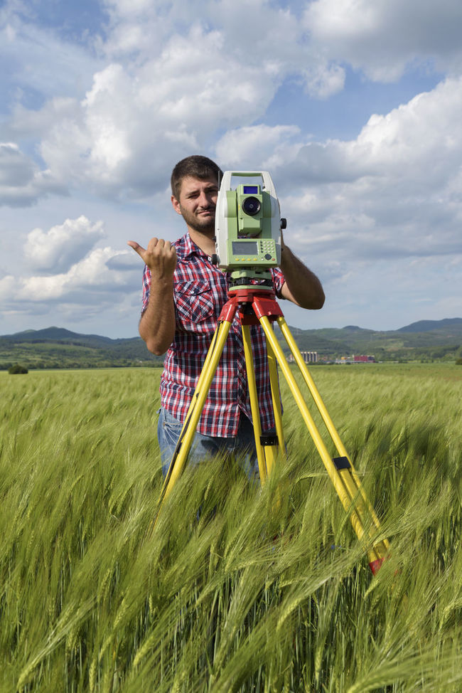 Land surveyor working with total station in wheat field Agriculture Bluetooth Field Industry Land Wheat Field Working Beard Caucasian Engineer Equipment Geodesy Land Surveyor Location Measurement Network One Man Only Point Pole Professional Occupation Surveying Technology Total Station Tripod Wireless Technology