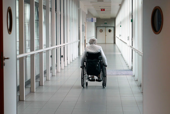 Real People Rear View The Way Forward Belgium Hospital Medical Disabled woman Corridor Solitude Wheelchair Abandoned