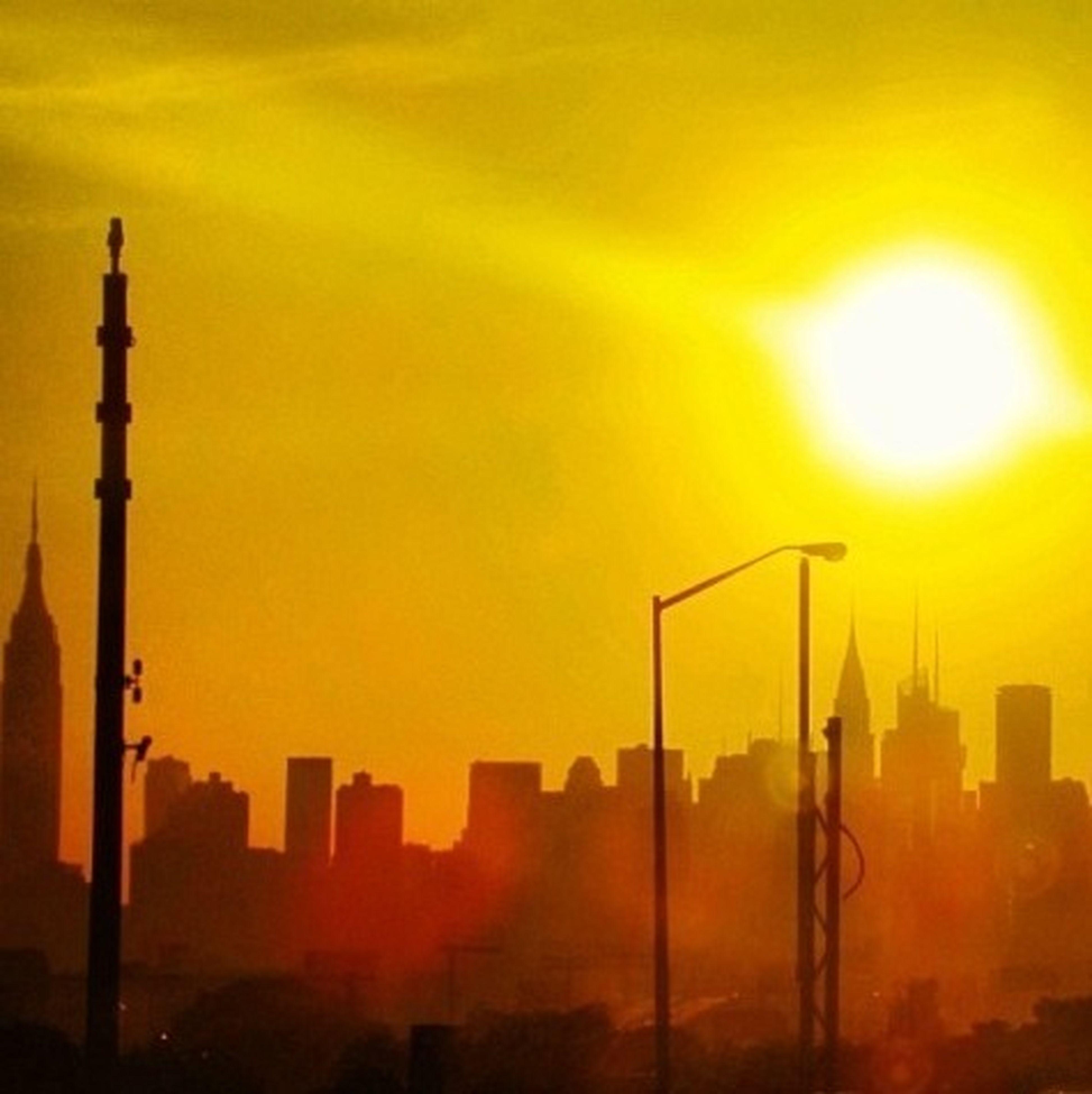 sunset, building exterior, architecture, built structure, city, orange color, tower, skyscraper, cityscape, tall - high, silhouette, sun, sky, communications tower, urban skyline, capital cities, street light, building, sunlight, city life