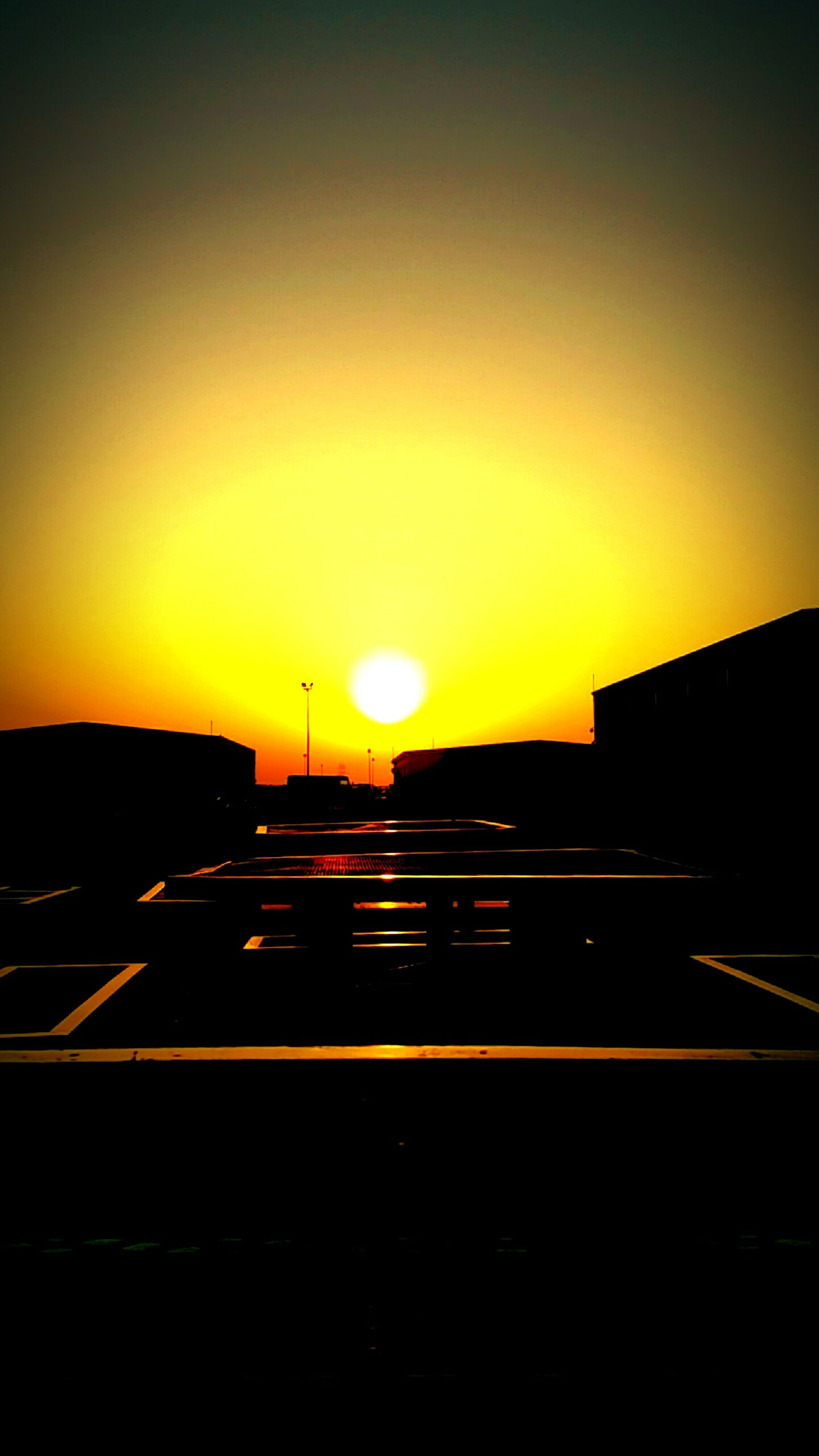 sunset, orange color, silhouette, sun, transportation, copy space, clear sky, sky, sunlight, built structure, road, scenics, dark, architecture, car, beauty in nature, building exterior, nature, outdoors, no people