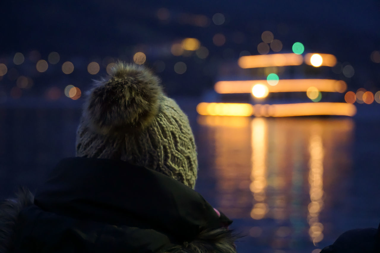 night, illuminated, rear view, real people, one person, focus on foreground, water, lifestyles, outdoors, sea, winter, nature, childhood, warm clothing, close-up, sky, people