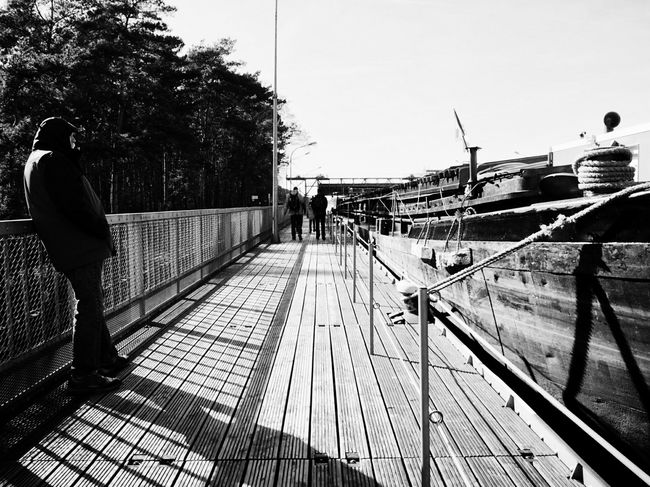 Silent Dialogue Silent Moment Boat Standing Alone StandingSolo Streetphotography Streetphoto_bw Streetscene Portrait Of A Man  Harbour Bw_collection Blackandwhite Black And White Vanishing Point Telling Stories Differently Light And Shadow Watching Boats Up Close Street Photography Monochrome Photography