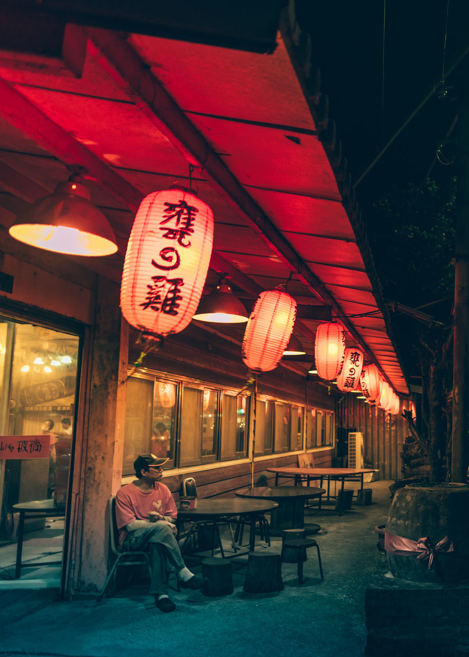 chinese lantern, text, illuminated, lantern, full length, hanging, real people, night, built structure, architecture, outdoors, building exterior, one person, people