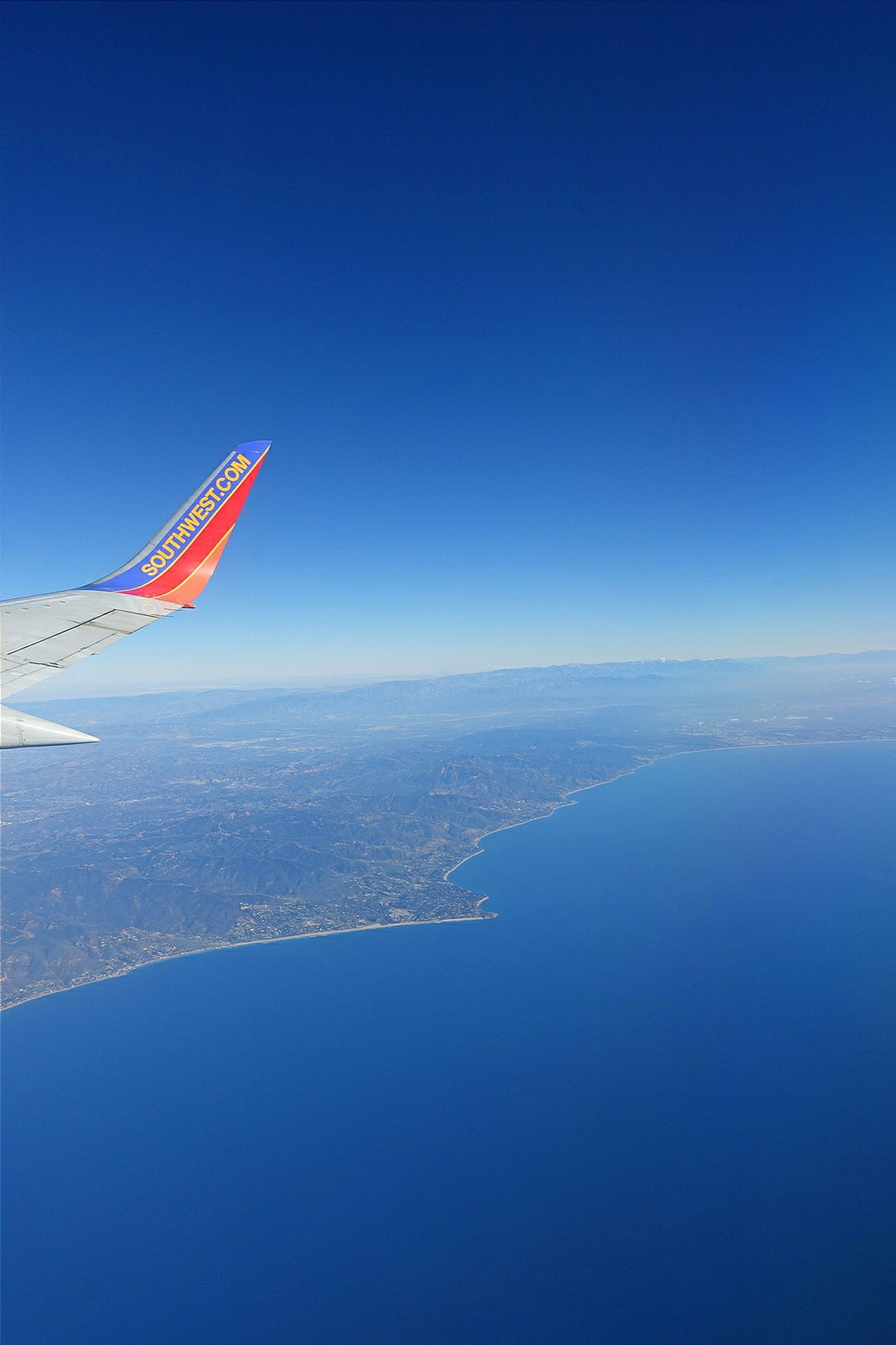 blue, clear sky, copy space, flying, sea, water, aerial view, mid-air, nature, transportation, waterfront, scenics, beauty in nature, travel, air vehicle, outdoors, cityscape, mode of transport, day, no people