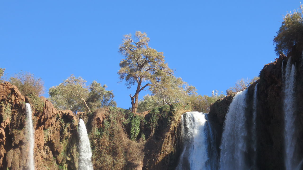 ouzoud waterfalls in morocco Beauty In Nature Blue Clear Sky Day Growth Landscape Nature No People Outdoors Ouzoud Falls Scenics Sky Tranquility Travel Destinations Tree Water Waterfalls