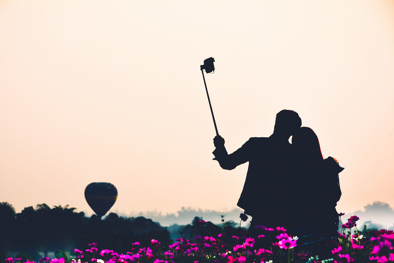 Silhouette Couple Taking Selfie Against Clear Sky