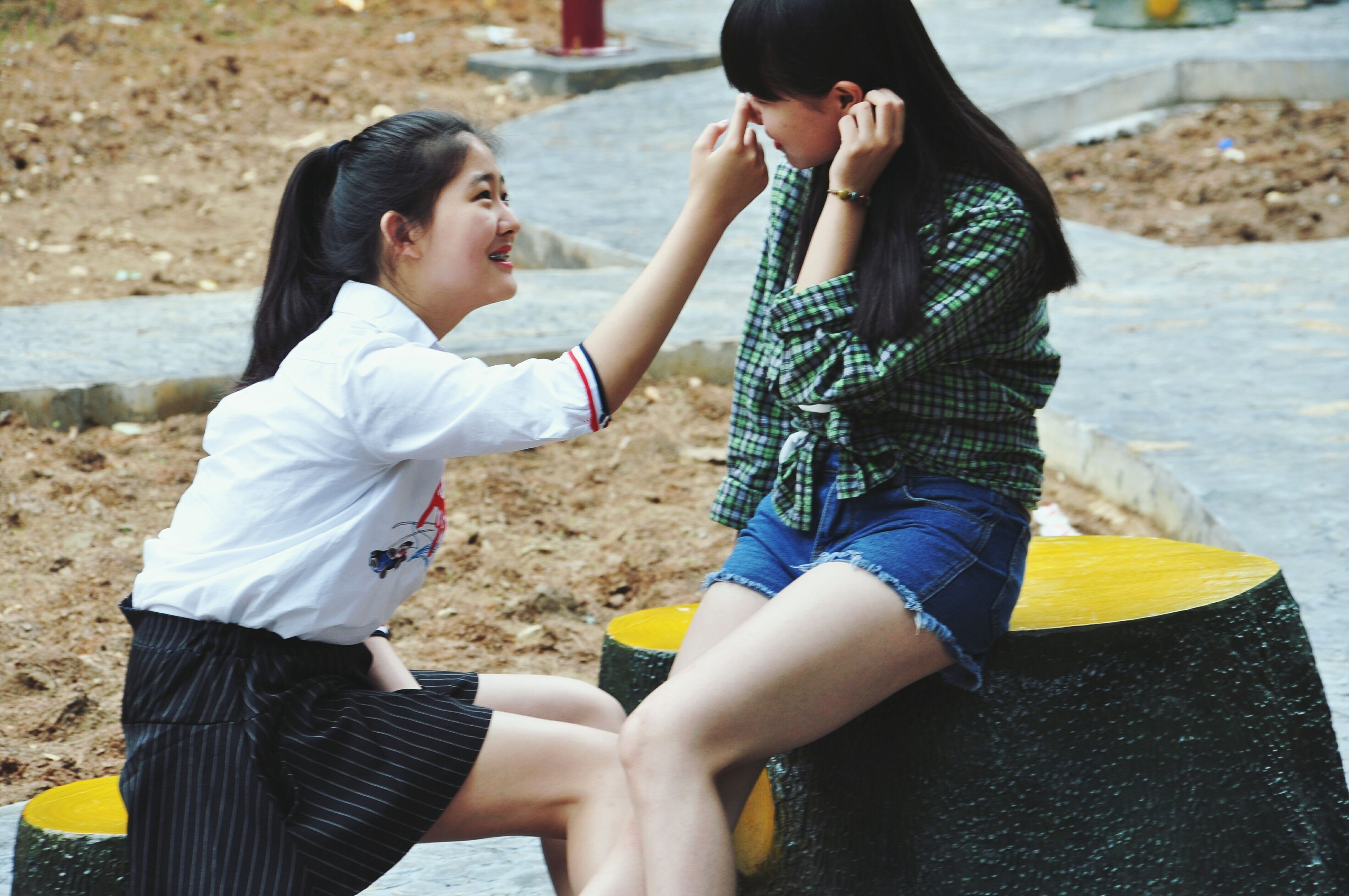 two people, real people, childhood, girls, outdoors, togetherness, leisure activity, casual clothing, day, love, side view, elementary age, lifestyles, bonding, young women, sunlight, sitting, happiness, boys, young adult, human hand