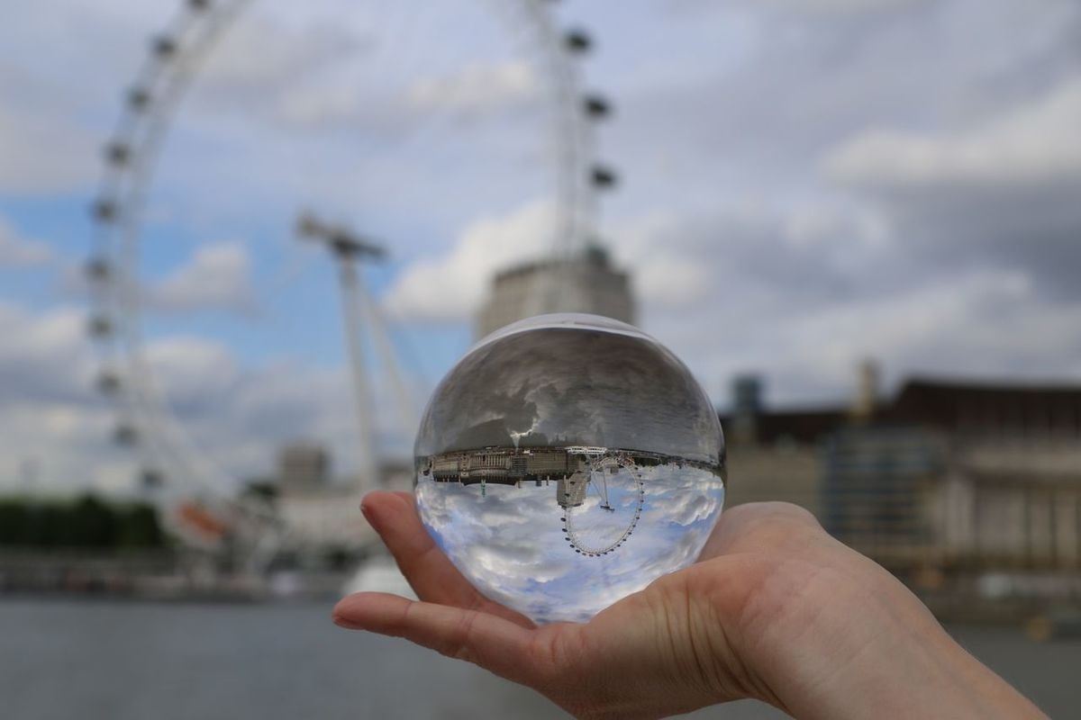 EyeEm LOST IN London LondonEye Architecture Building Exterior Built Structure City Close-up Crystal Ball Day Focus On Foreground Holding Human Body Part Human Hand One Person Outdoors Real People Sky Water