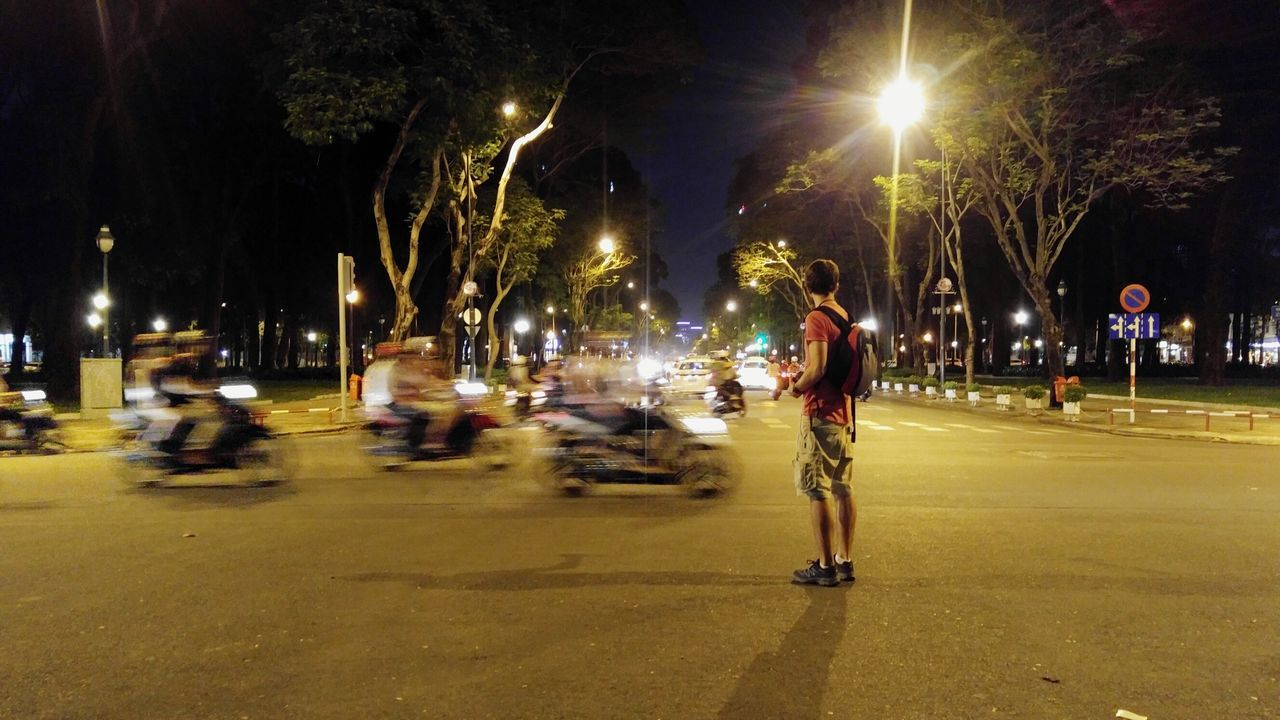Rear View Of Man Standing On Road In City At Night
