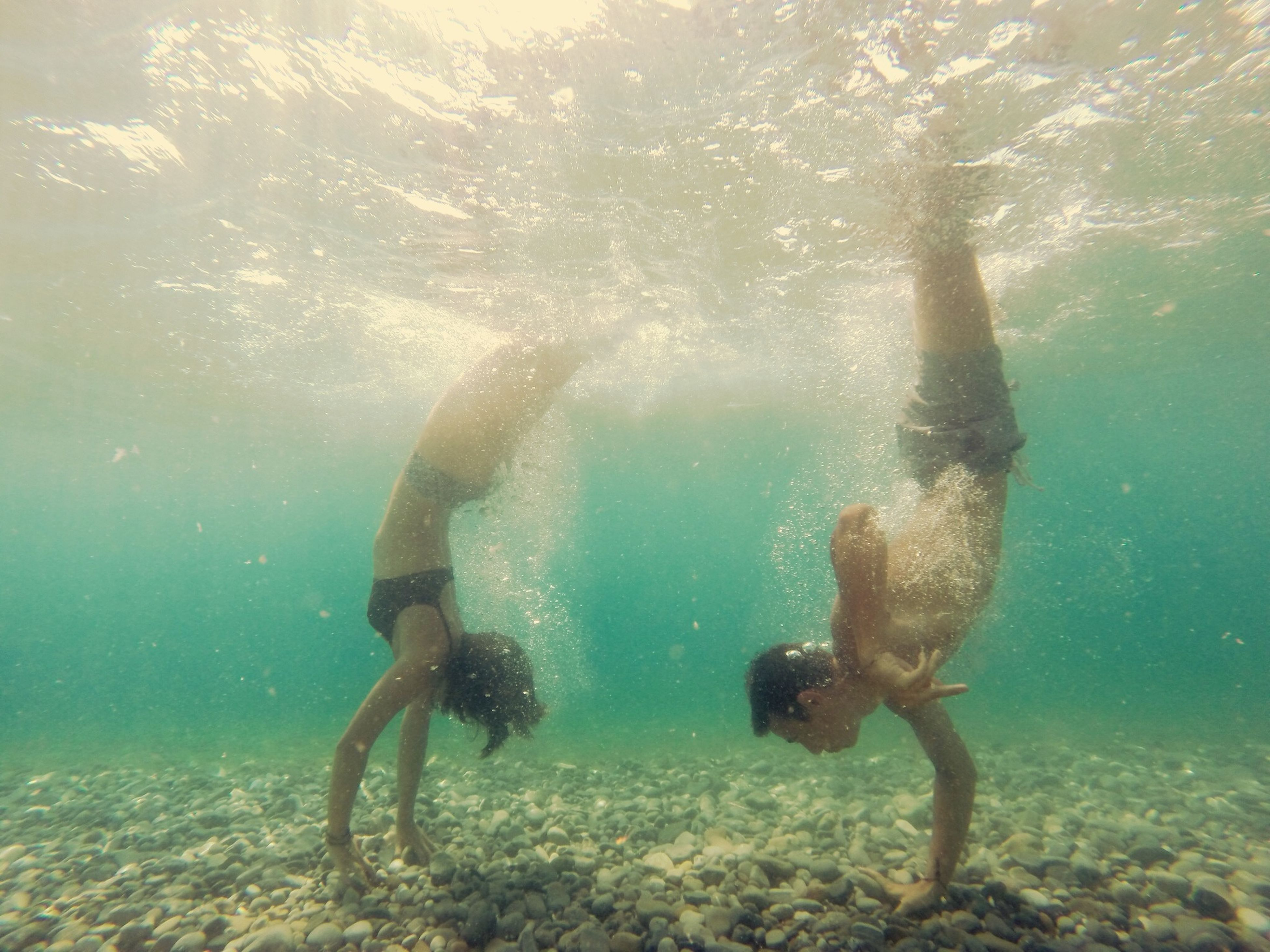 water, lifestyles, swimming, leisure activity, sea, underwater, animal themes, men, full length, motion, high angle view, one animal, sunlight, vacations, nature, blue, day, shirtless