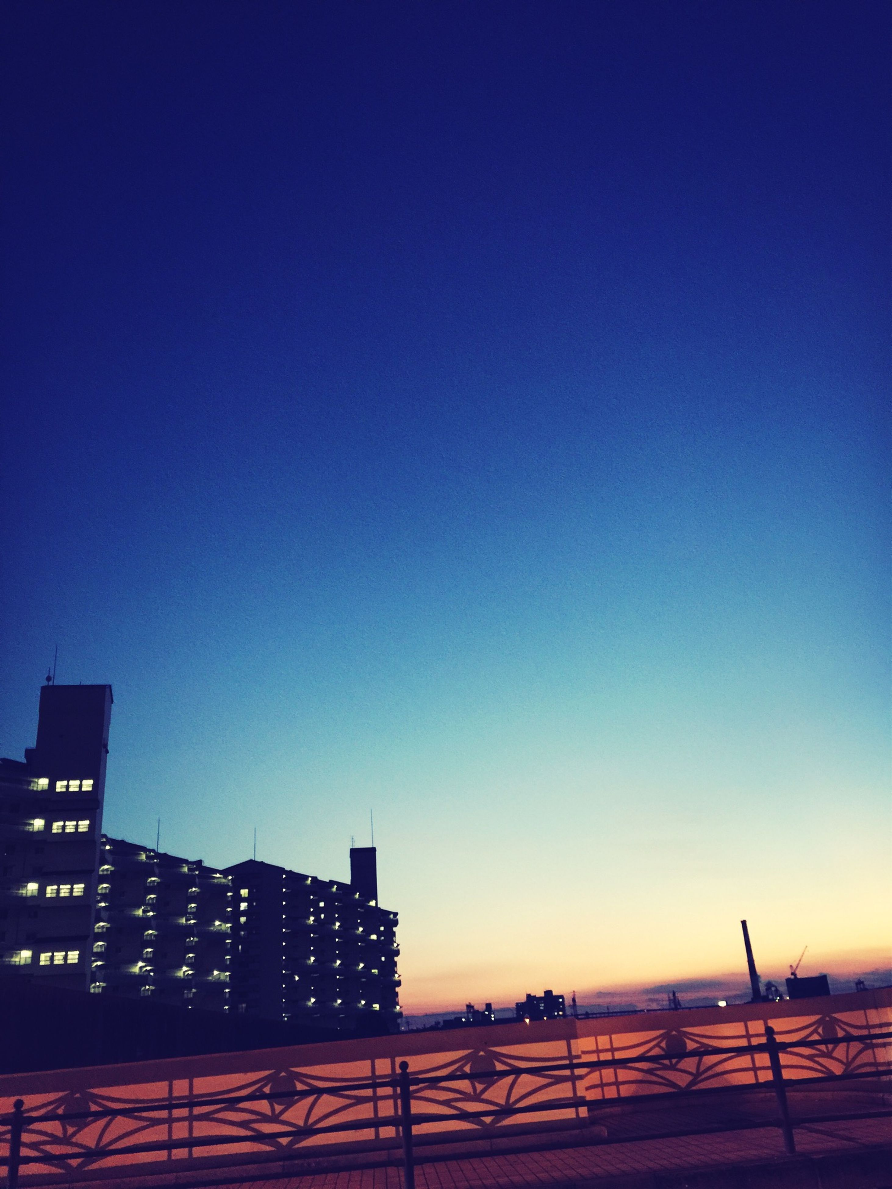 clear sky, copy space, architecture, built structure, building exterior, blue, sunset, silhouette, city, dusk, outdoors, low angle view, no people, building, development, sunlight, railing, sky, industry, connection