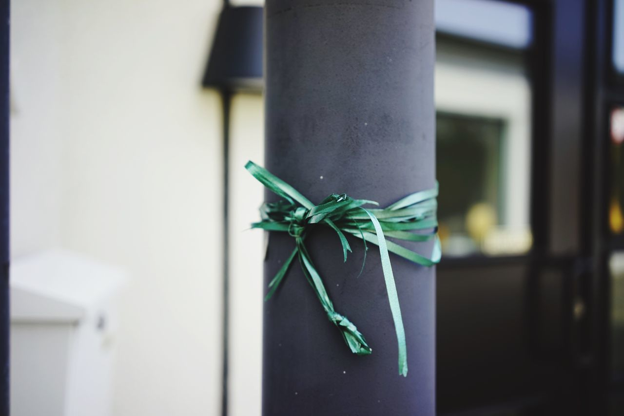 Close-Up Of Green Ribbon Tied Up On Pole