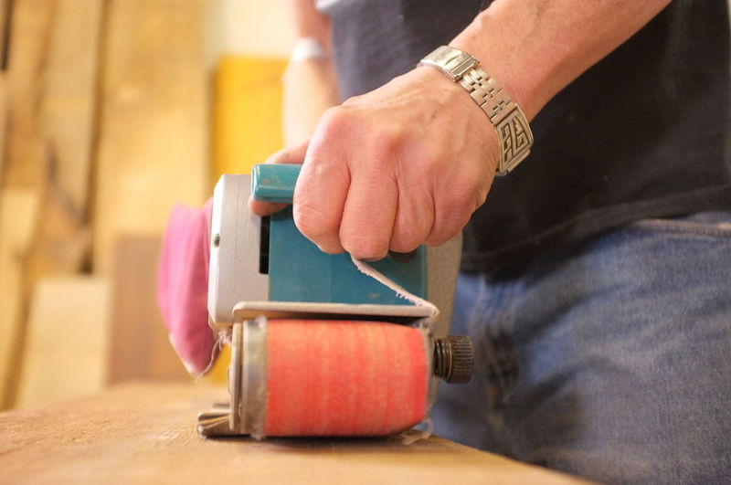 Worker uses roller to smooth wood Close-up Construction Cropped Focus On Foreground Hand Handyman Holding Human Finger Indoors  Leisure Activity Lifestyles Men Mid Section Midsection Part Of Person Red Roller Selective Focus Tools, Unrecognizable Person Woodworker Worker