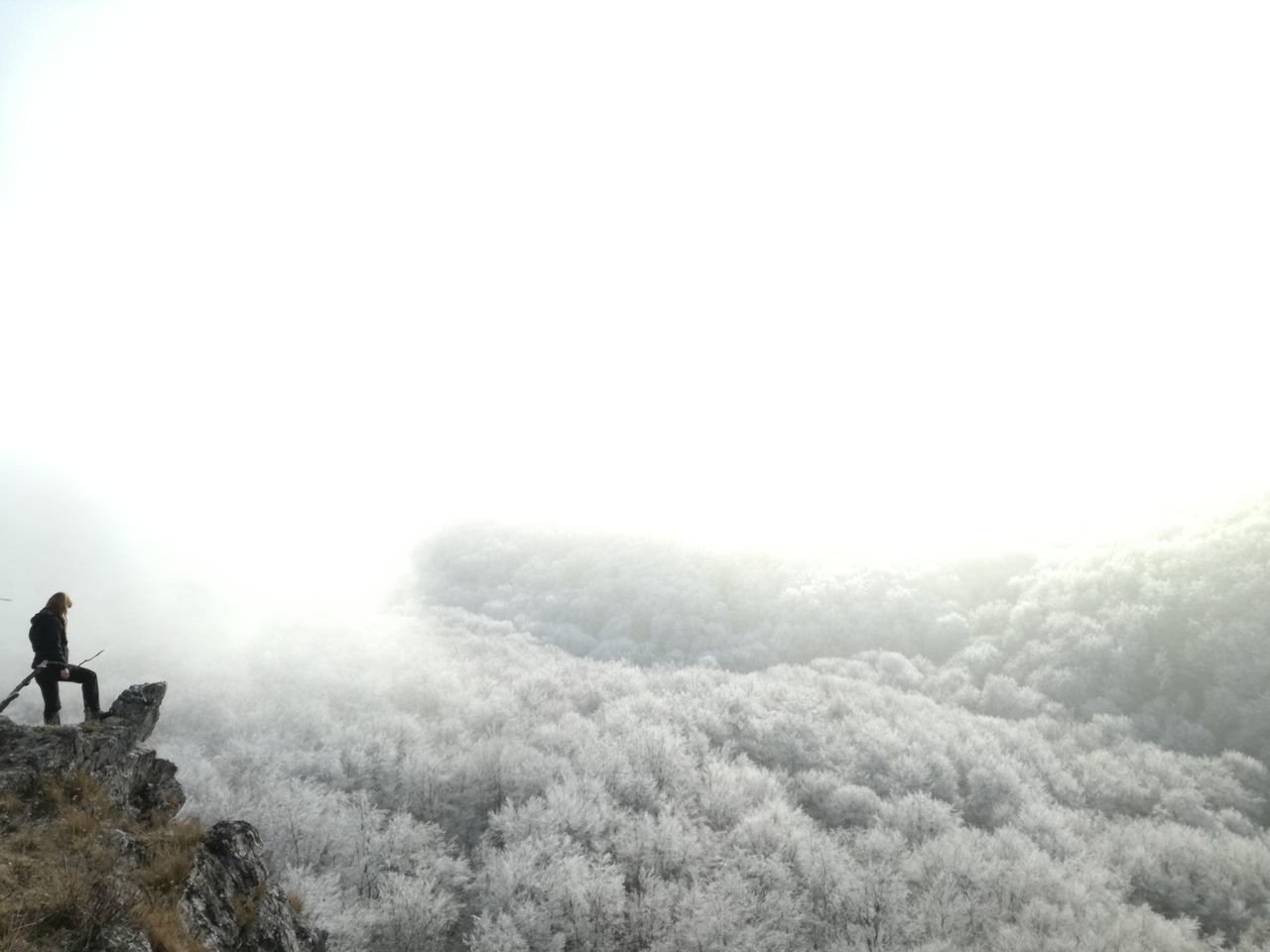 Person Standing On Cliff Against Sky During Winter