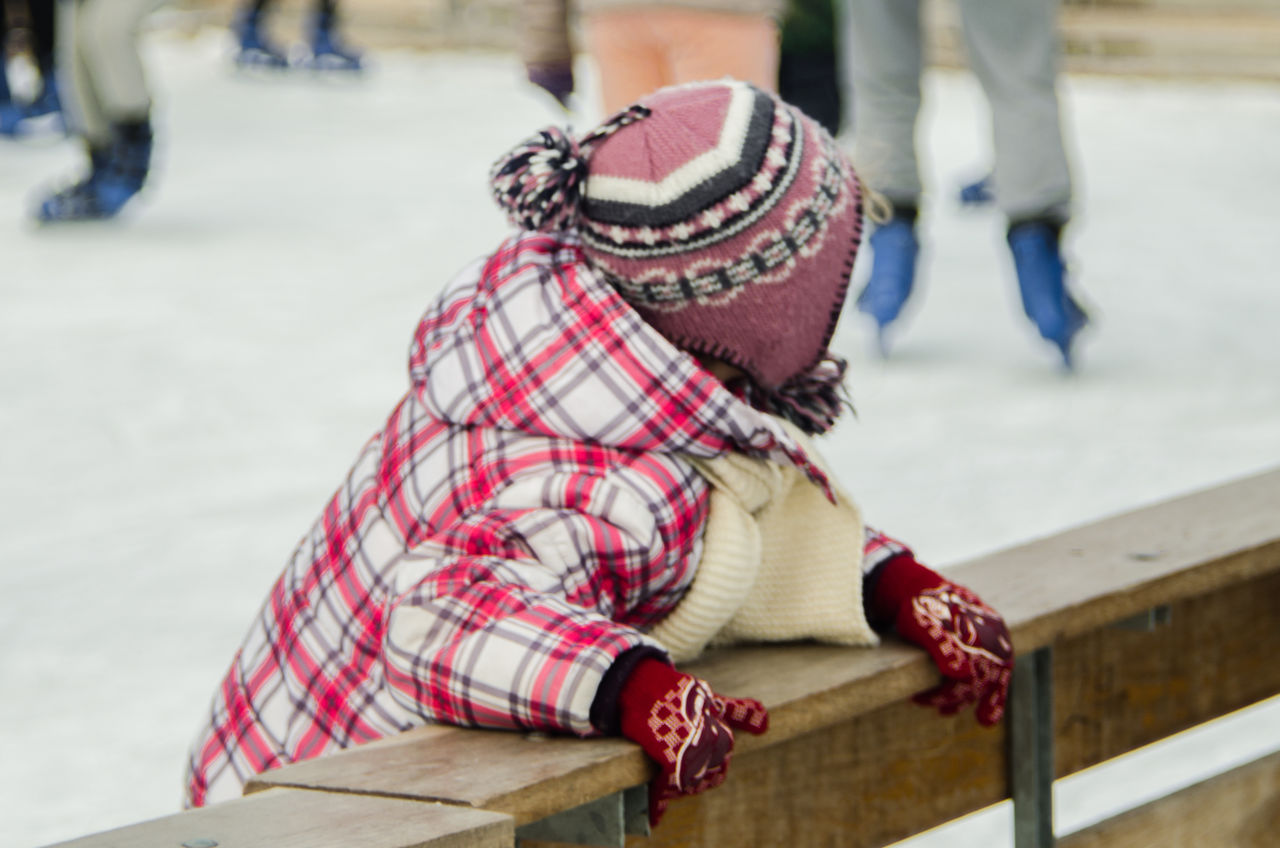 Blurred Background Casual Clothing Child Close-up Day Girl Happiness Ice Kid Leisure Activity Low Section Outdoors People Real People Sitting Skating Snow Wood Wooden Fence