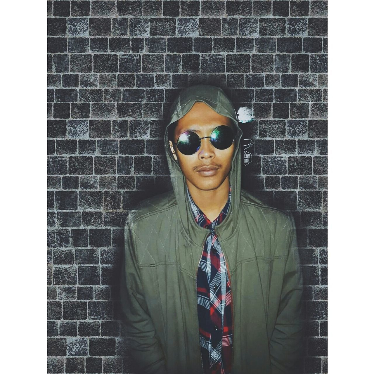 brick wall, front view, young adult, standing, waist up, one person, young men, real people, sunglasses, portrait, looking at camera, young women, well-dressed, lifestyles, smiling, men, indoors, day, people