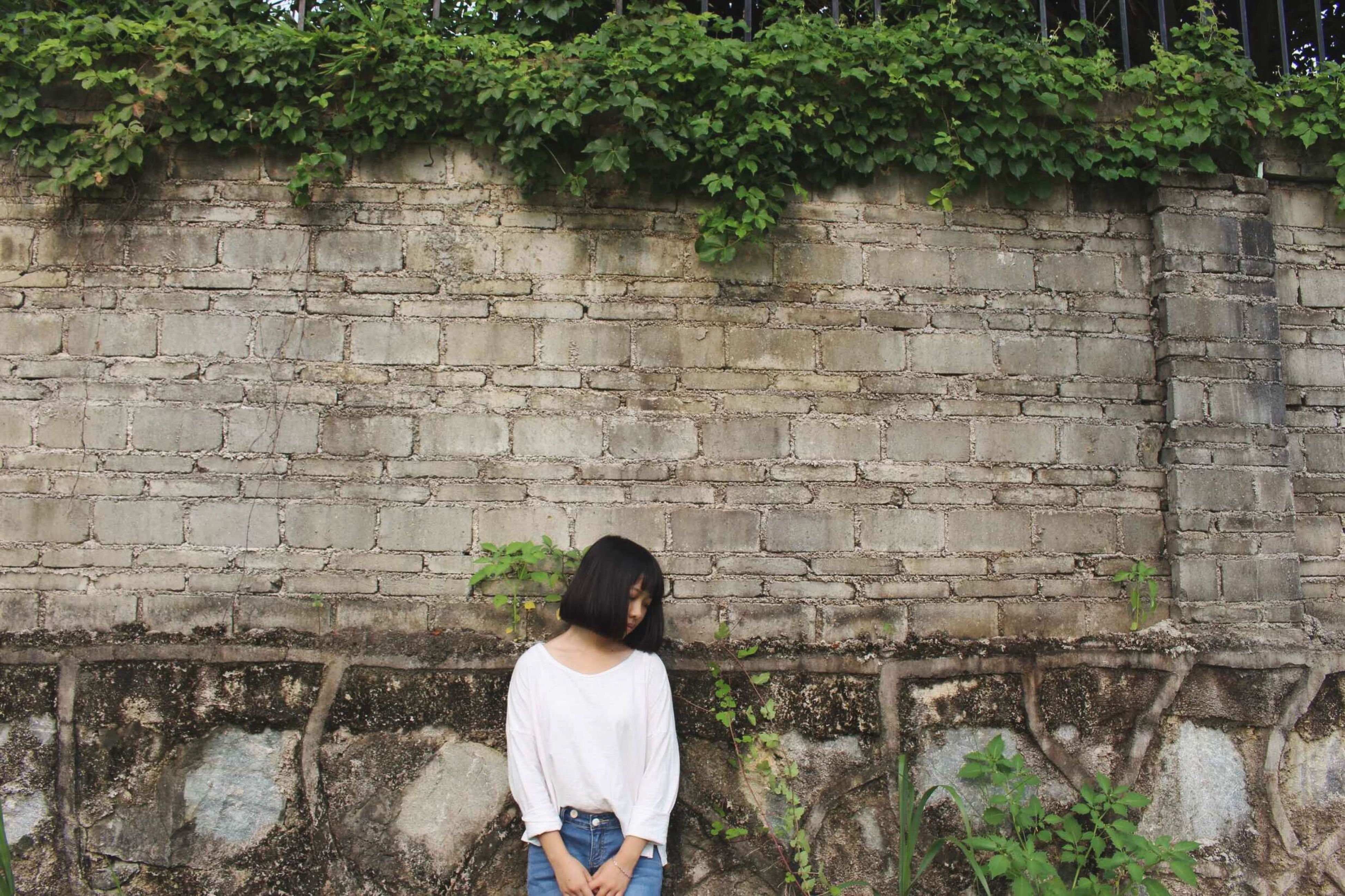 lifestyles, casual clothing, leisure activity, standing, built structure, architecture, wall - building feature, stone wall, plant, rear view, full length, building exterior, brick wall, three quarter length, person, young adult, wall, day