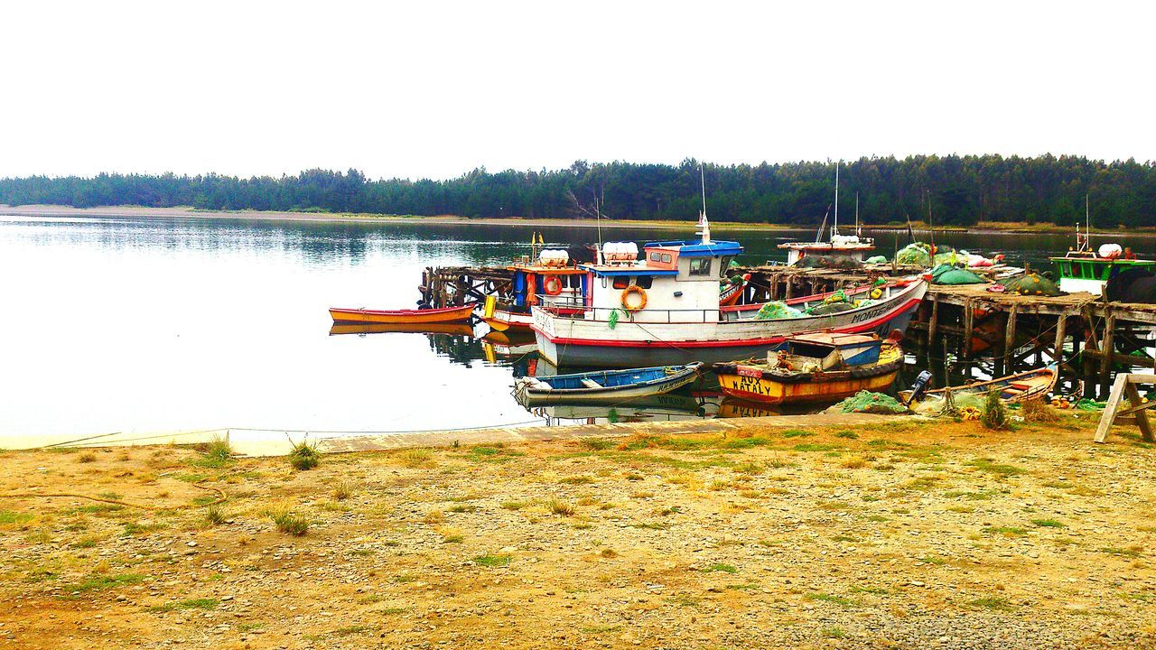 nautical vessel, moored, water, transportation, boat, nature, mode of transport, no people, tranquility, clear sky, day, riverbank, tranquil scene, river, scenics, tree, outdoors, beauty in nature, sky