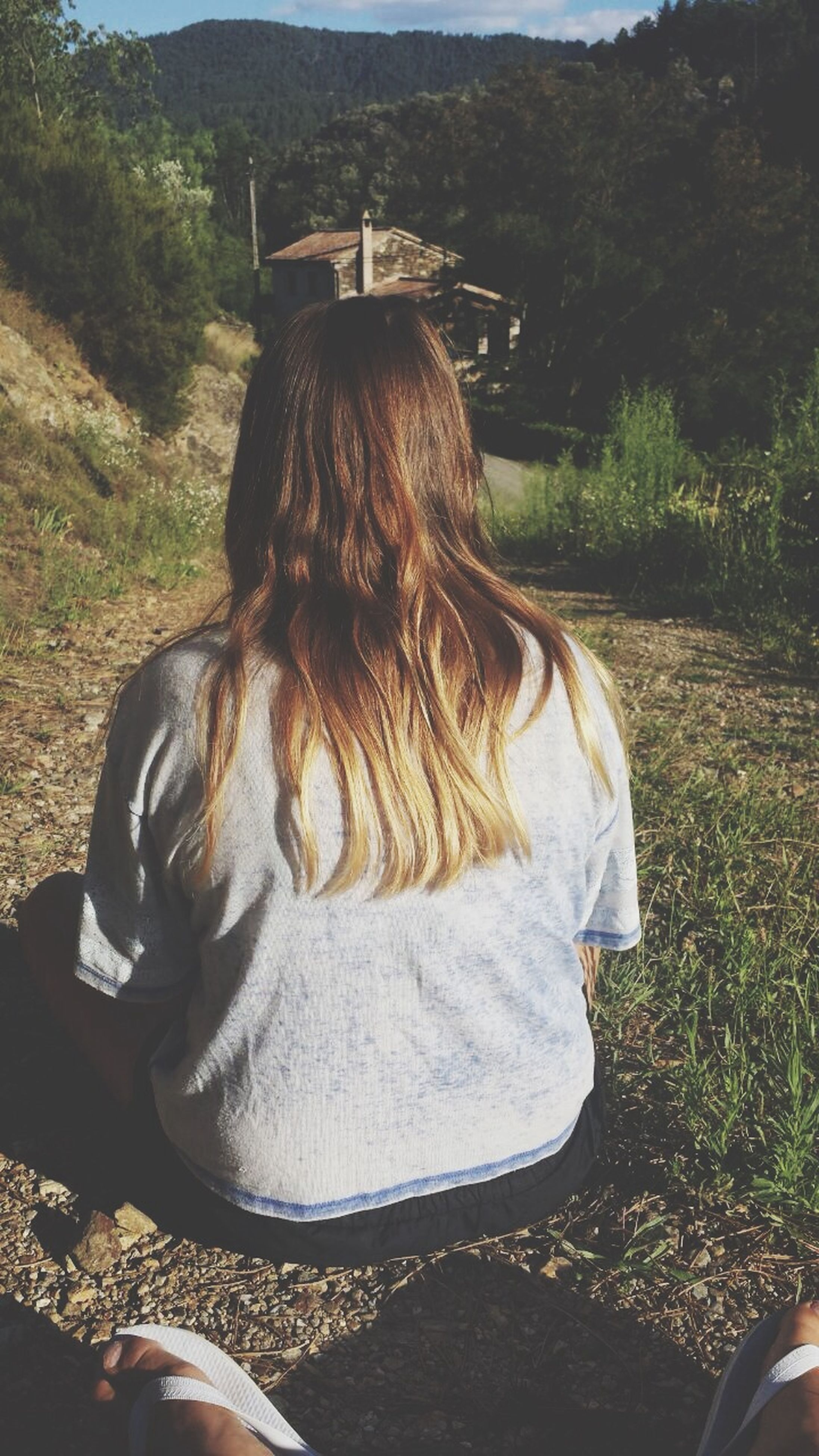 rear view, field, grass, day, outdoors, landscape, person, nature, relaxation, resting, sunlight, lifestyles, leisure activity, long hair, casual clothing, tranquility, sitting, plant