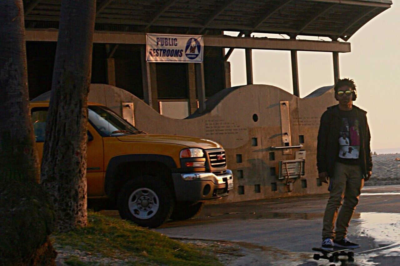 full length, standing, one person, real people, transportation, architecture, rear view, built structure, car, men, day, land vehicle, building exterior, one man only, outdoors, occupation, adult, only men, adults only, people