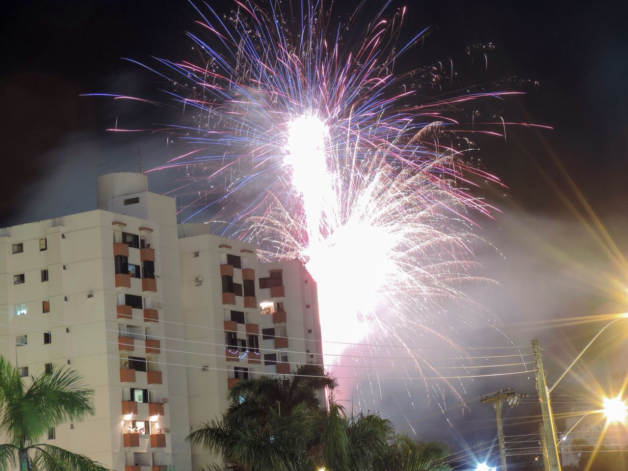 night, celebration, illuminated, firework display, firework - man made object, long exposure, glowing, architecture, building exterior, low angle view, exploding, built structure, event, no people, arts culture and entertainment, outdoors, firework, motion, sky, city, multi colored, tree