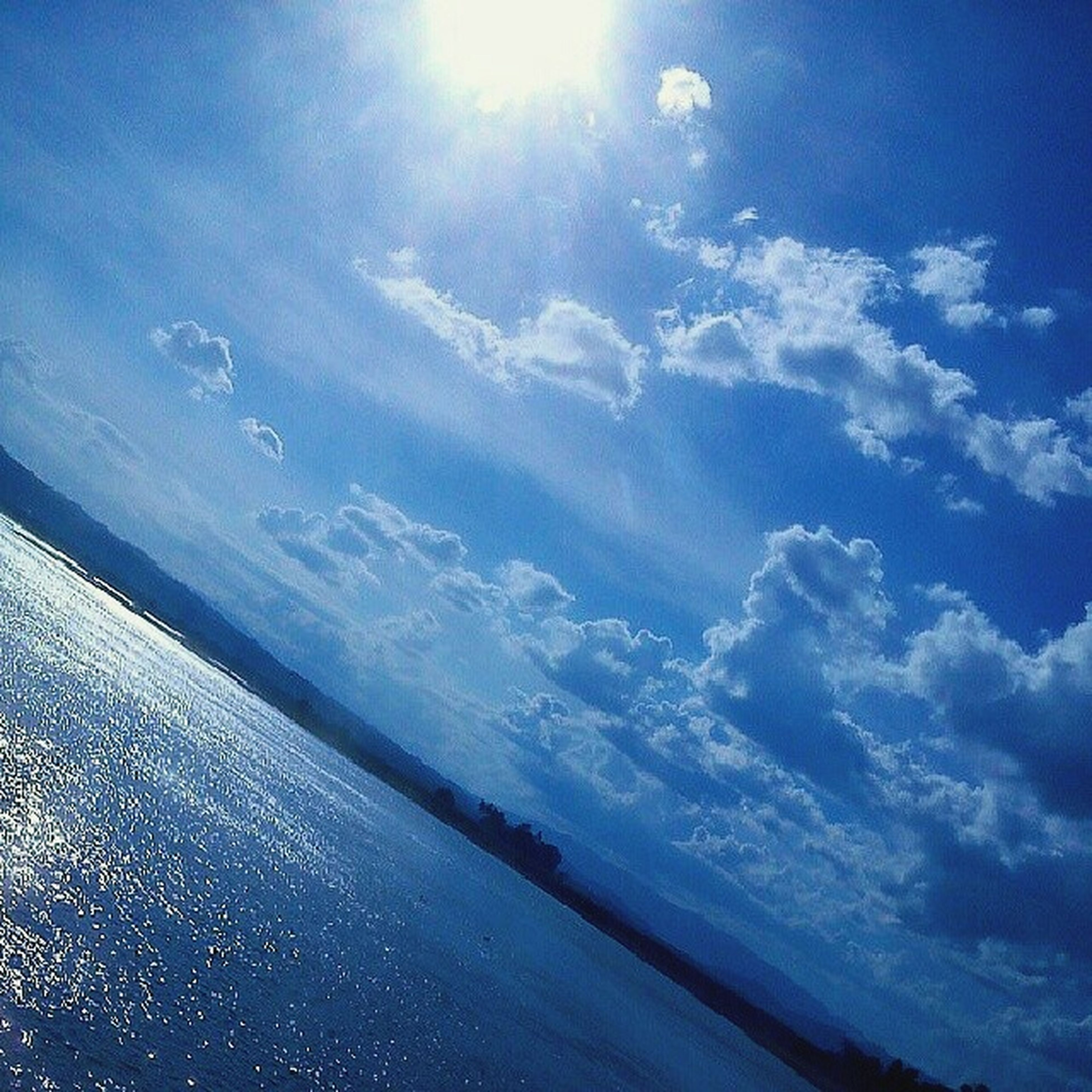 sky, blue, beauty in nature, scenics, sunlight, cloud - sky, sunbeam, tranquility, nature, tranquil scene, sea, sun, cloud, day, water, aerial view, idyllic, sunny, outdoors, lens flare