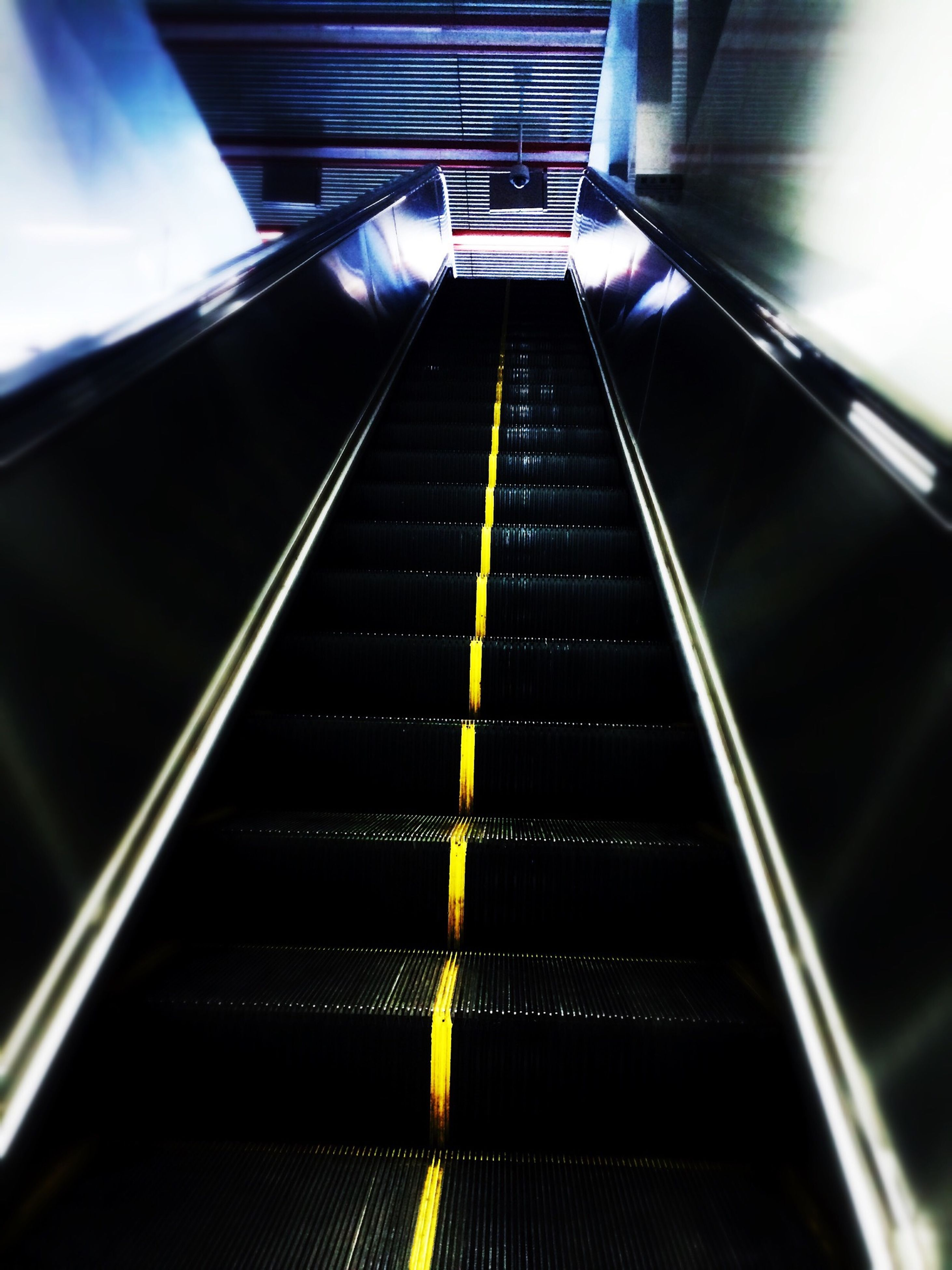 escalator, indoors, steps and staircases, the way forward, diminishing perspective, railing, steps, staircase, modern, transportation, vanishing point, low angle view, convenience, technology, metal, high angle view, built structure, architecture, futuristic, no people