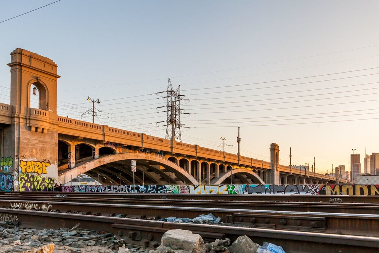 bridge - man made structure, connection, transportation, architecture, rail transportation, built structure, train - vehicle, railroad track, clear sky, city, cable, outdoors, sunset, building exterior, sky, day, no people, cityscape