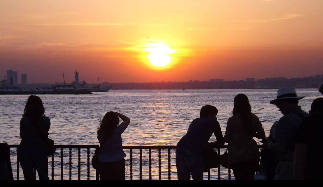 sunset, orange color, sea, silhouette, water, sun, men, sky, real people, women, leisure activity, standing, beauty in nature, lifestyles, sunlight, beach, nature, outdoors, scenics, togetherness, horizon over water, city, day, people