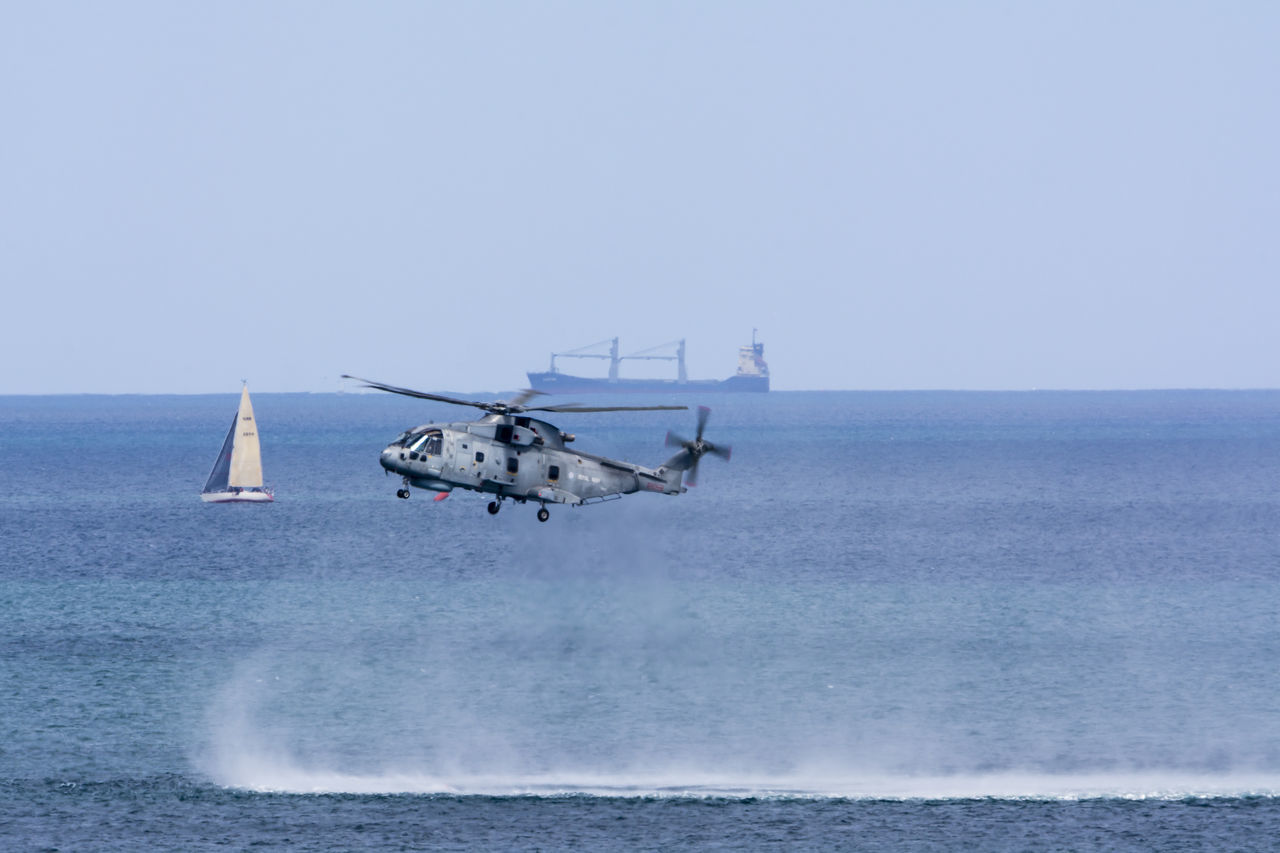 sea, horizon over water, water, transportation, helicopter, nautical vessel, clear sky, nature, waterfront, day, outdoors, motion, air vehicle, sky, beauty in nature, no people, military, wave