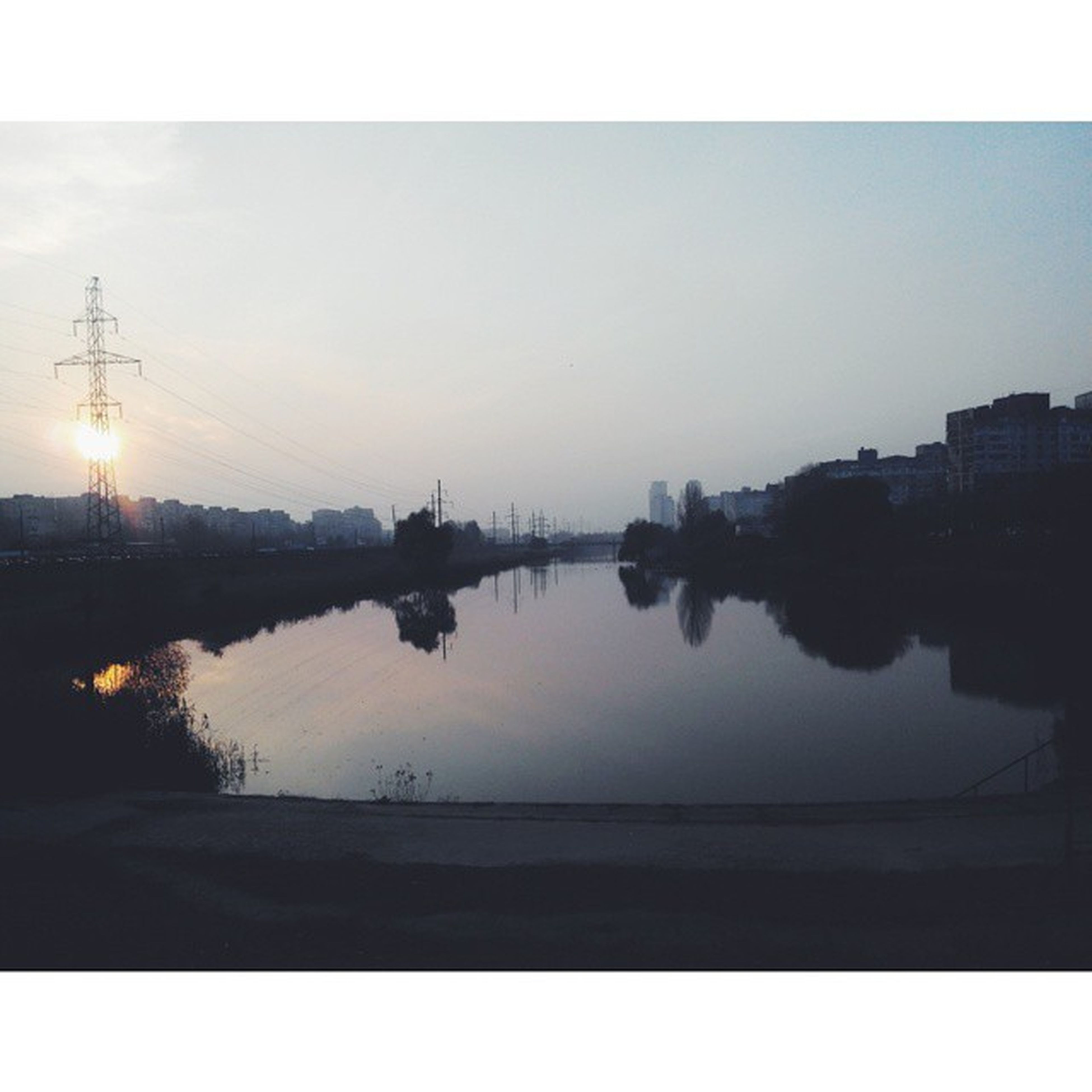 water, reflection, transfer print, silhouette, sky, sunset, lake, river, auto post production filter, clear sky, power line, electricity pylon, building exterior, tranquility, nature, tree, built structure, tranquil scene, scenics, beauty in nature