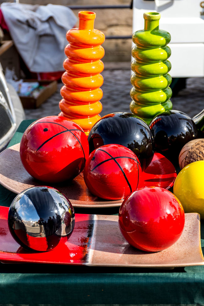 Variety of antique treasure items at Portugal market - ball, another ball, many balls, plates Abundance Arrangement Choice Close-up Collection Colorful Container Food And Drink Large Group Of Objects Multi Colored Organic Red Ripe Still Life Stone Balls Table Variation